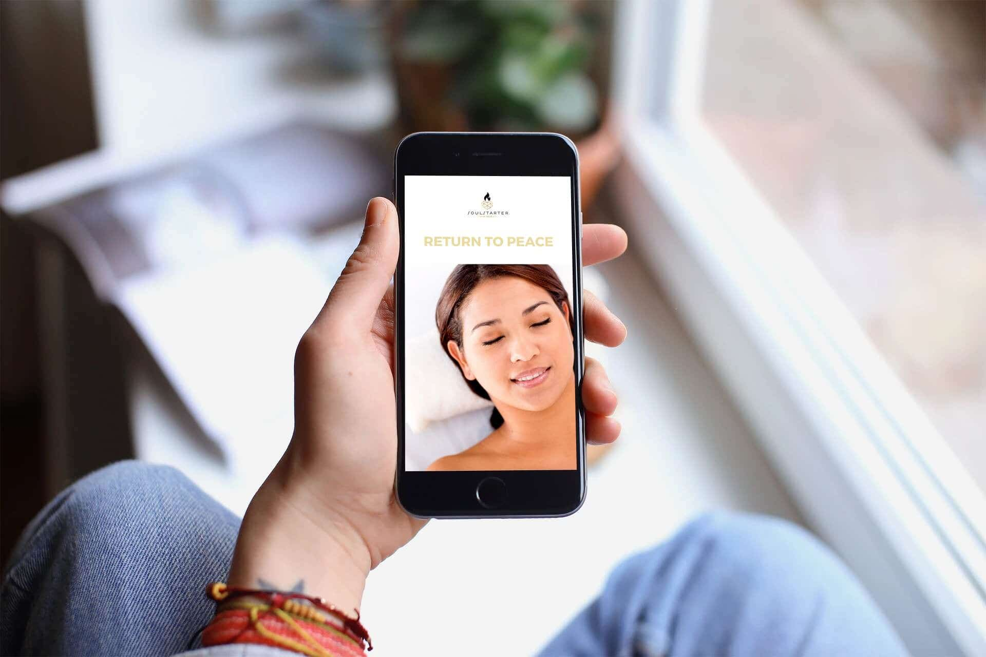 woman holding cellphone with screenshot of return to peace course
