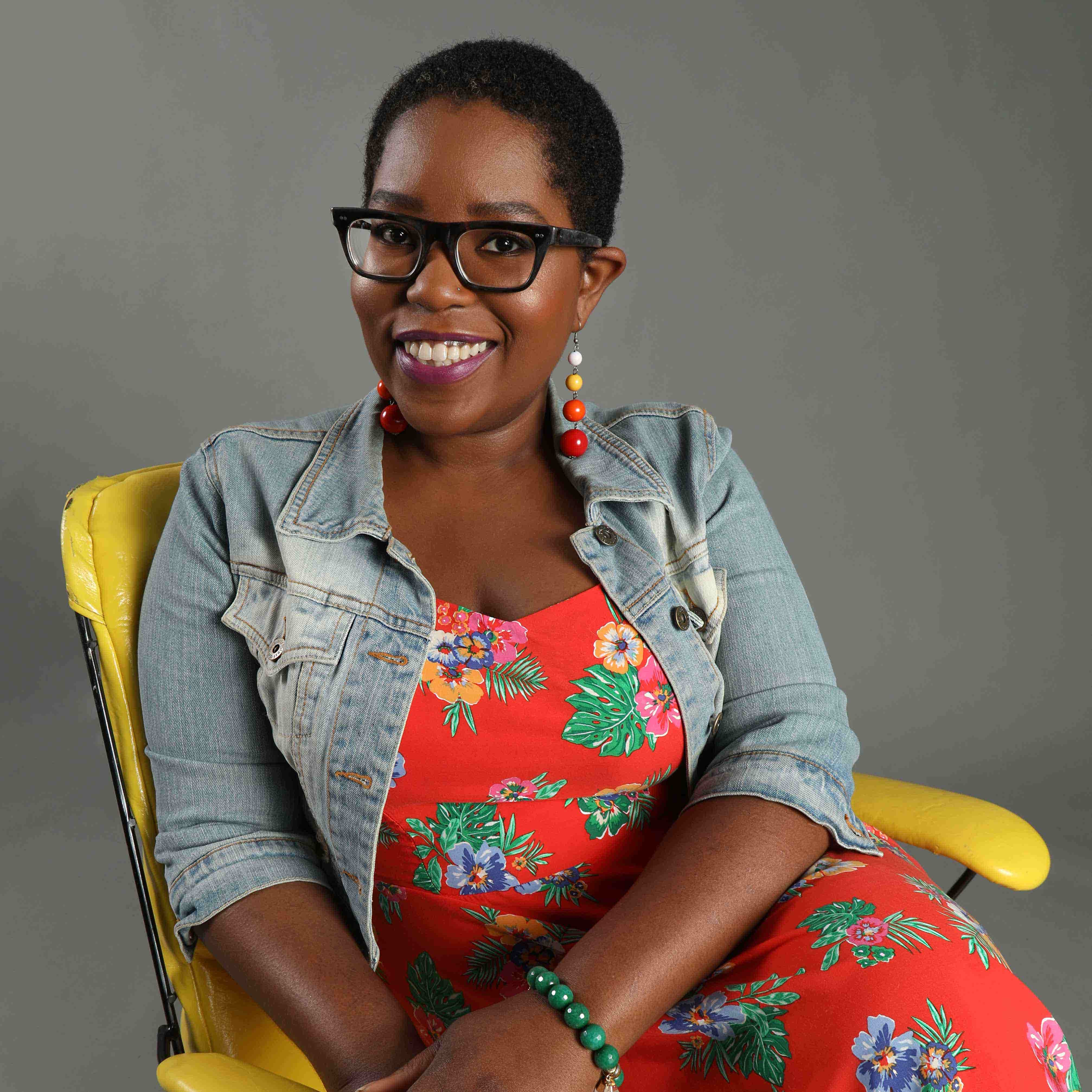 Dominique Wilson sitting in a yellow chair against a gray background. She is wearing dark brown glasses while smiling. She is also wearing an orange, tropics inspired sundress with a light blue jean jacket on top along with a pair of dangling earrings with white, yellow, orange, and yellow balls.