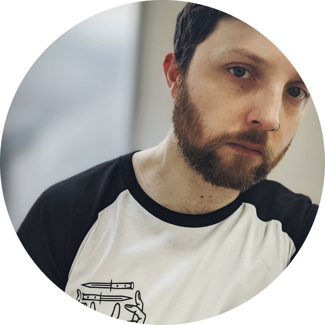 Chris is a while male with dark brown and reddish hair and a beard. He has a nose ring in his right nostril. He wears a black and white t-shirt and looks toward you with a studious expression.