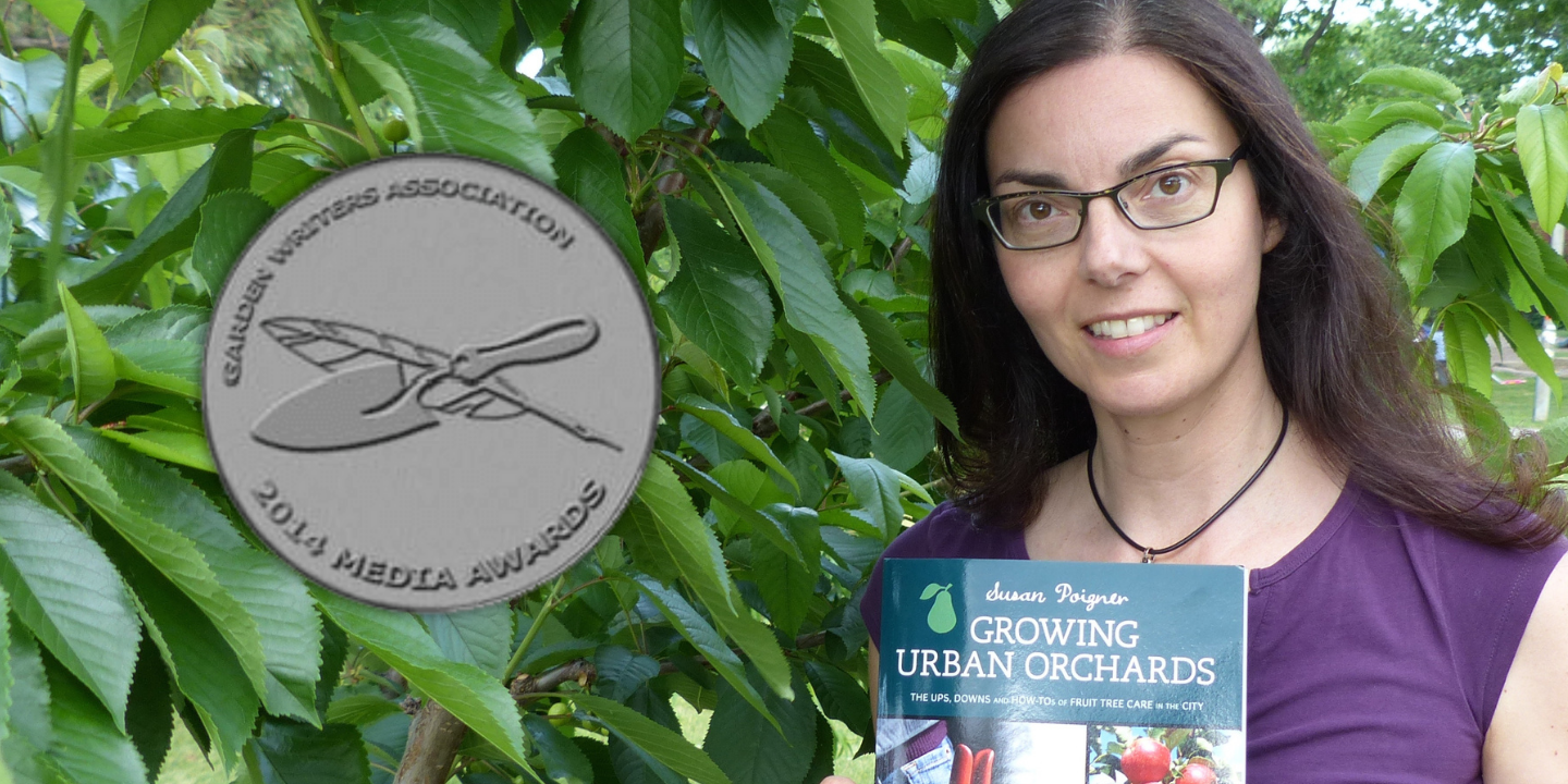 Susan Poizner with a copy of her award-winning book in front of a cherry tree