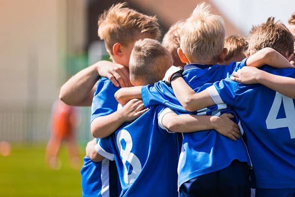 Kids in blue team shirt huddling