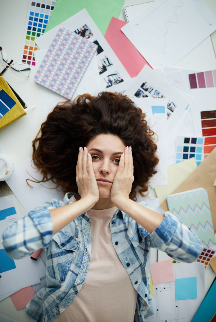 Woman lying on the floor surrounded by bit of paper and general chaos