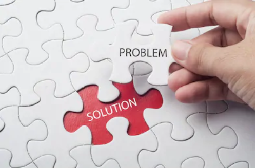 Hand holding a piece of a jigsaw that says problem