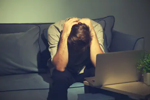 Young man at home suffering next to his laptop