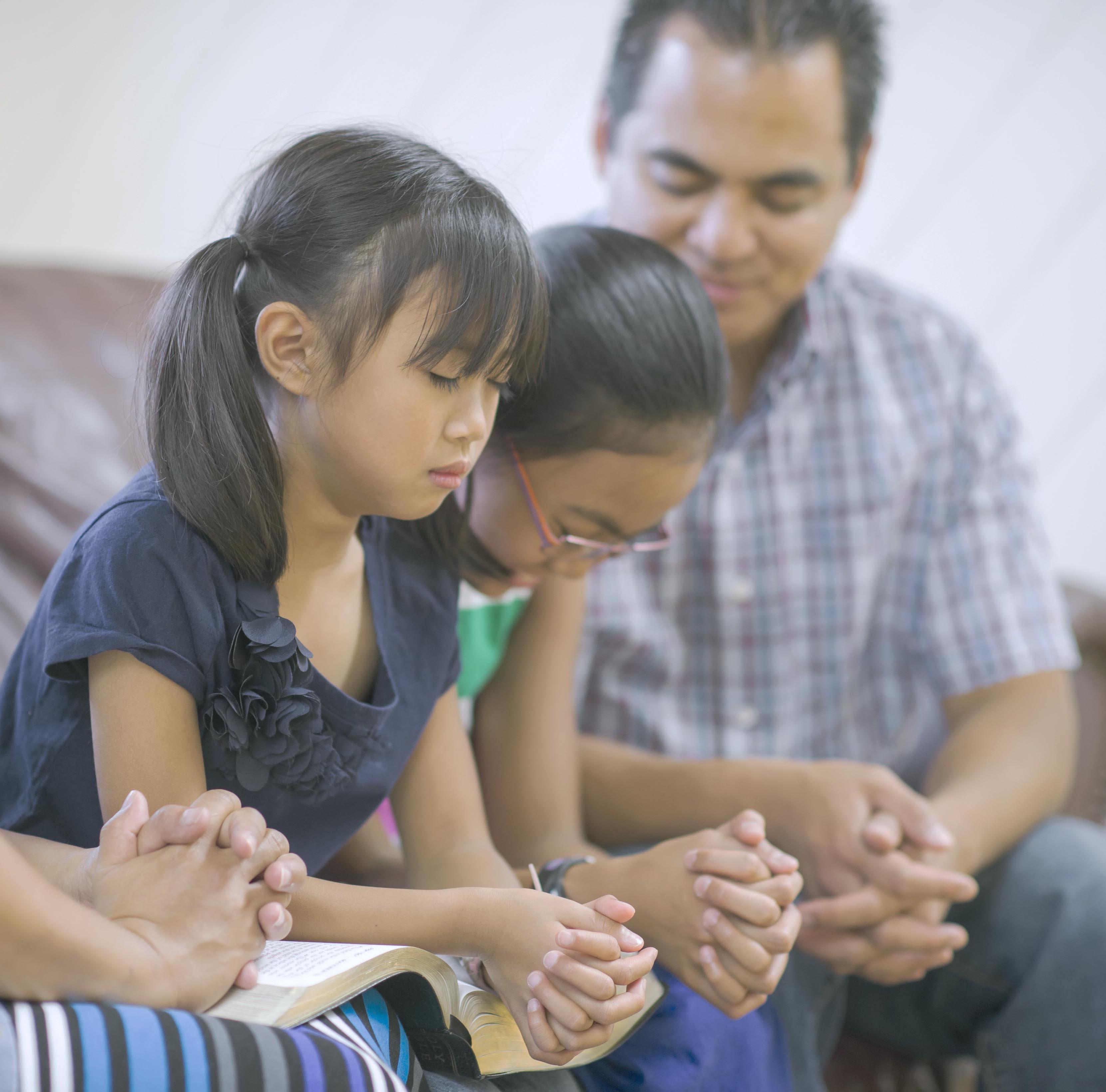 Two girls praying with dad