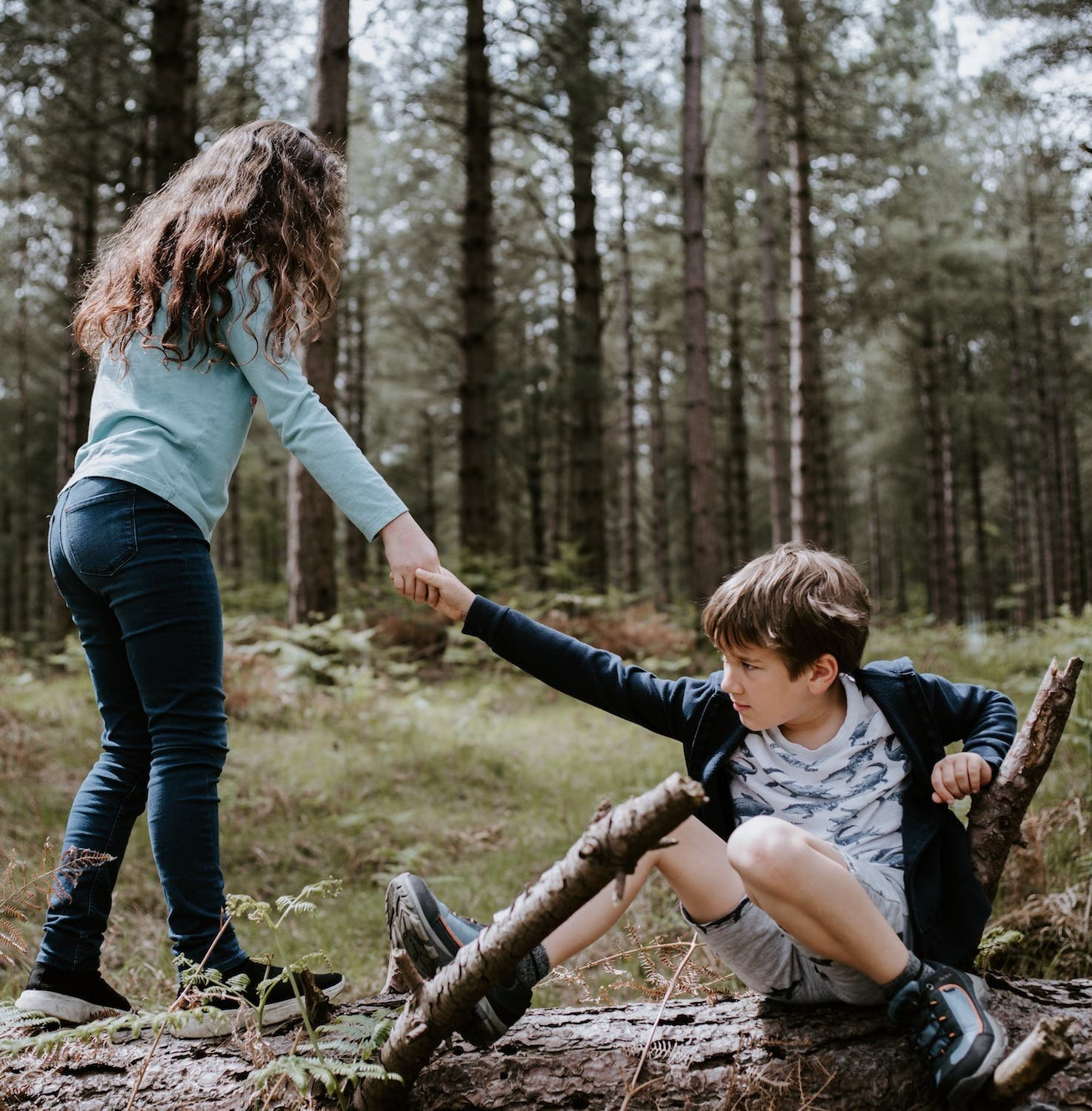 Girl helping boy up from sitting down