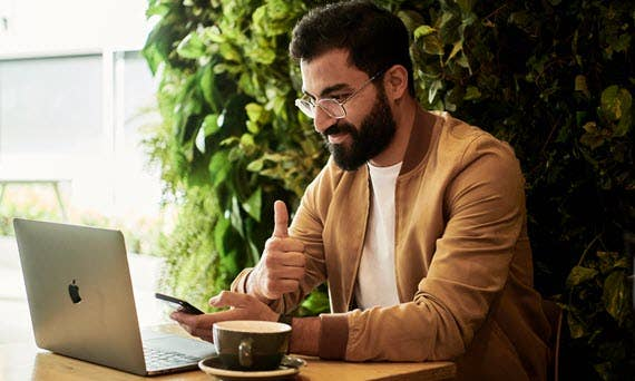 Man at Computer with Phone Negotiating