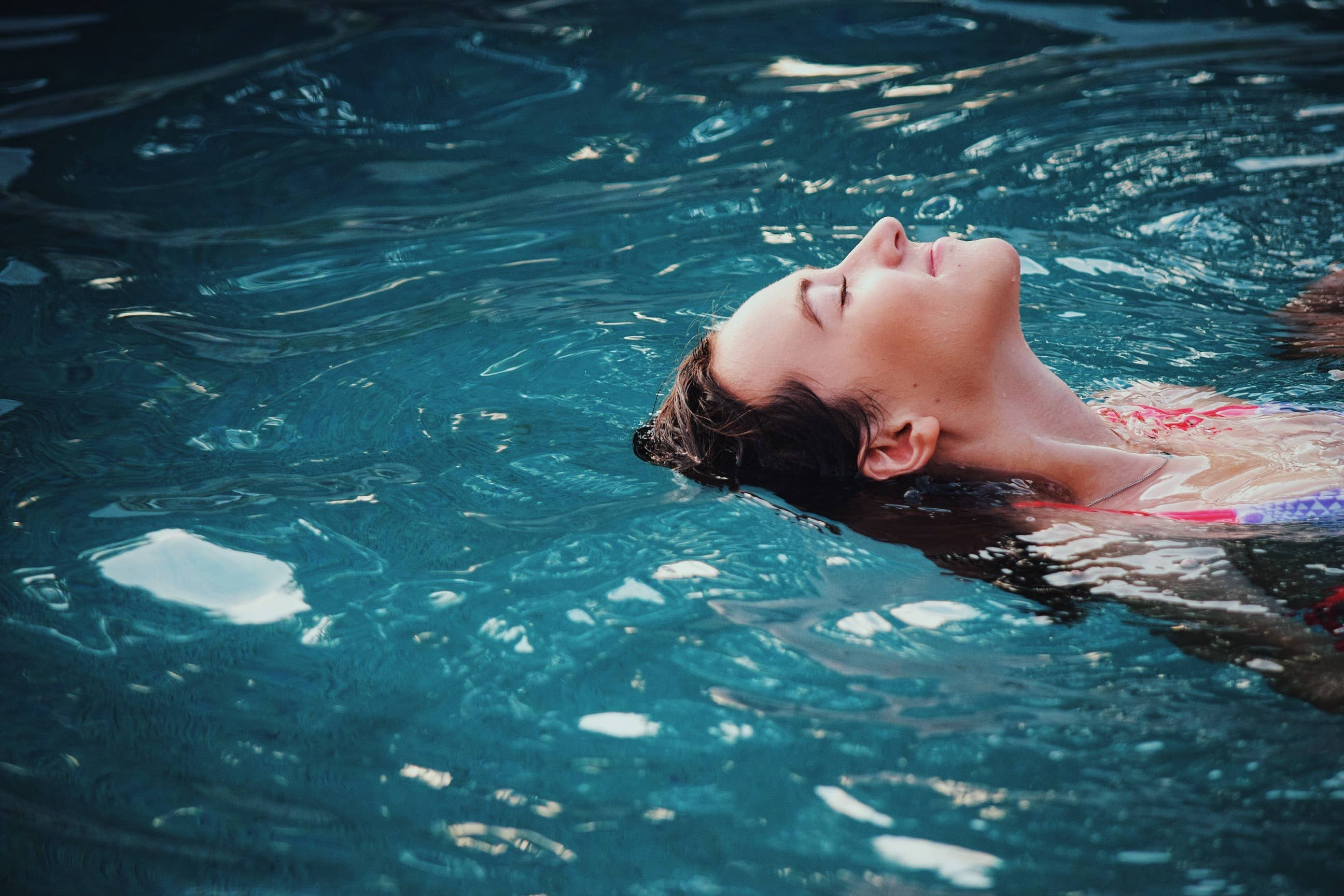 Alt= 'Person floating on their back in blue water'