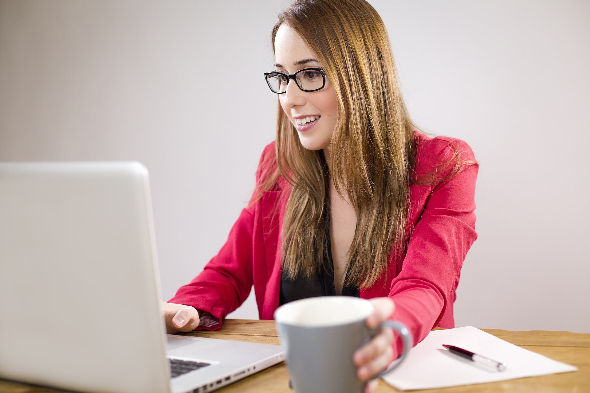 woman in pink blazer with laptop and coffee