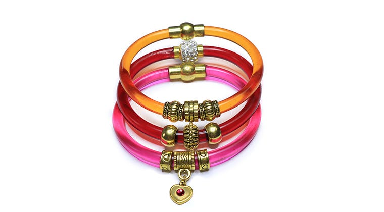 Stack of pink, red and orange resin bracelets strung with large-holed gold metal beads.