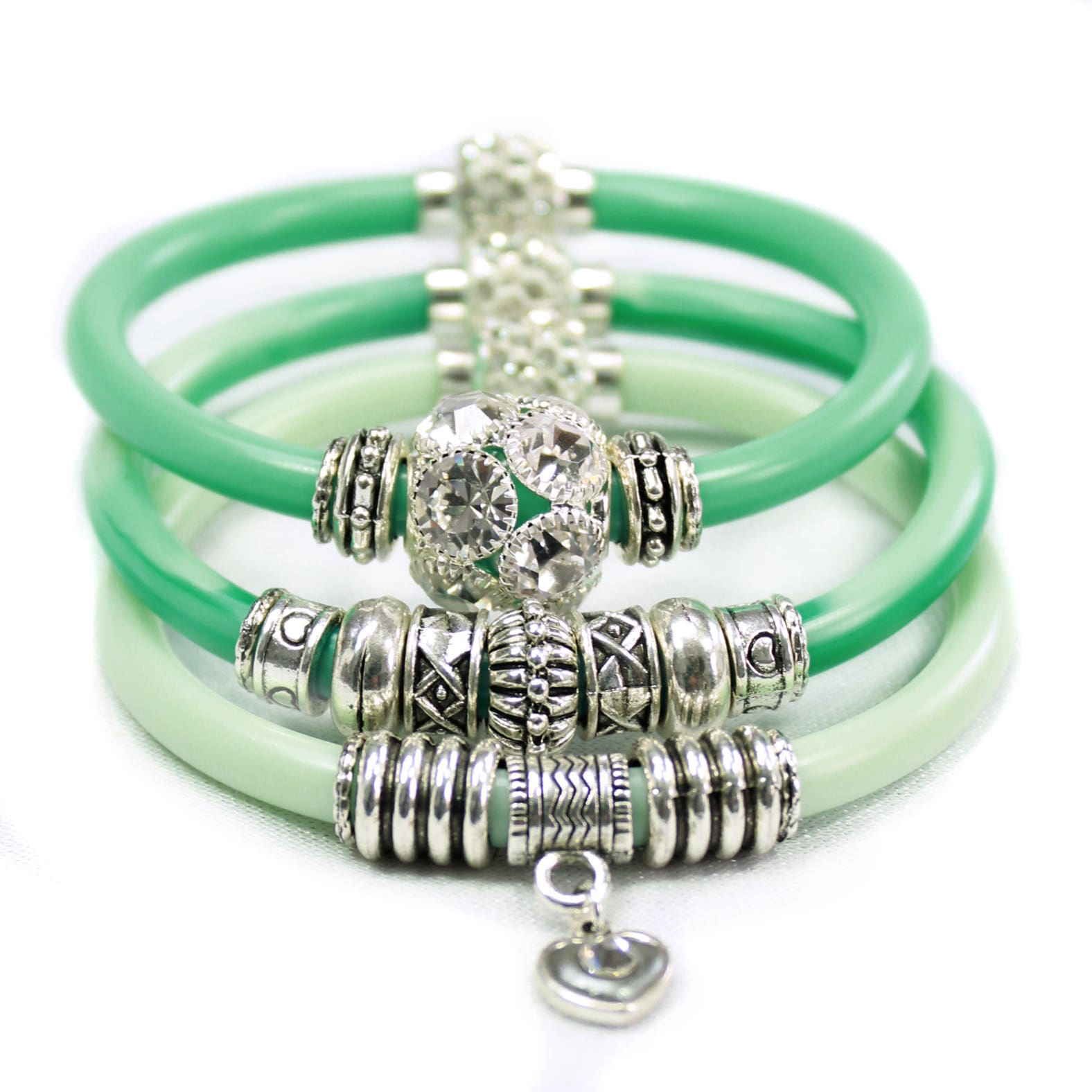 Stack of 3 green resin bracelets with silver beads and charms attached.
