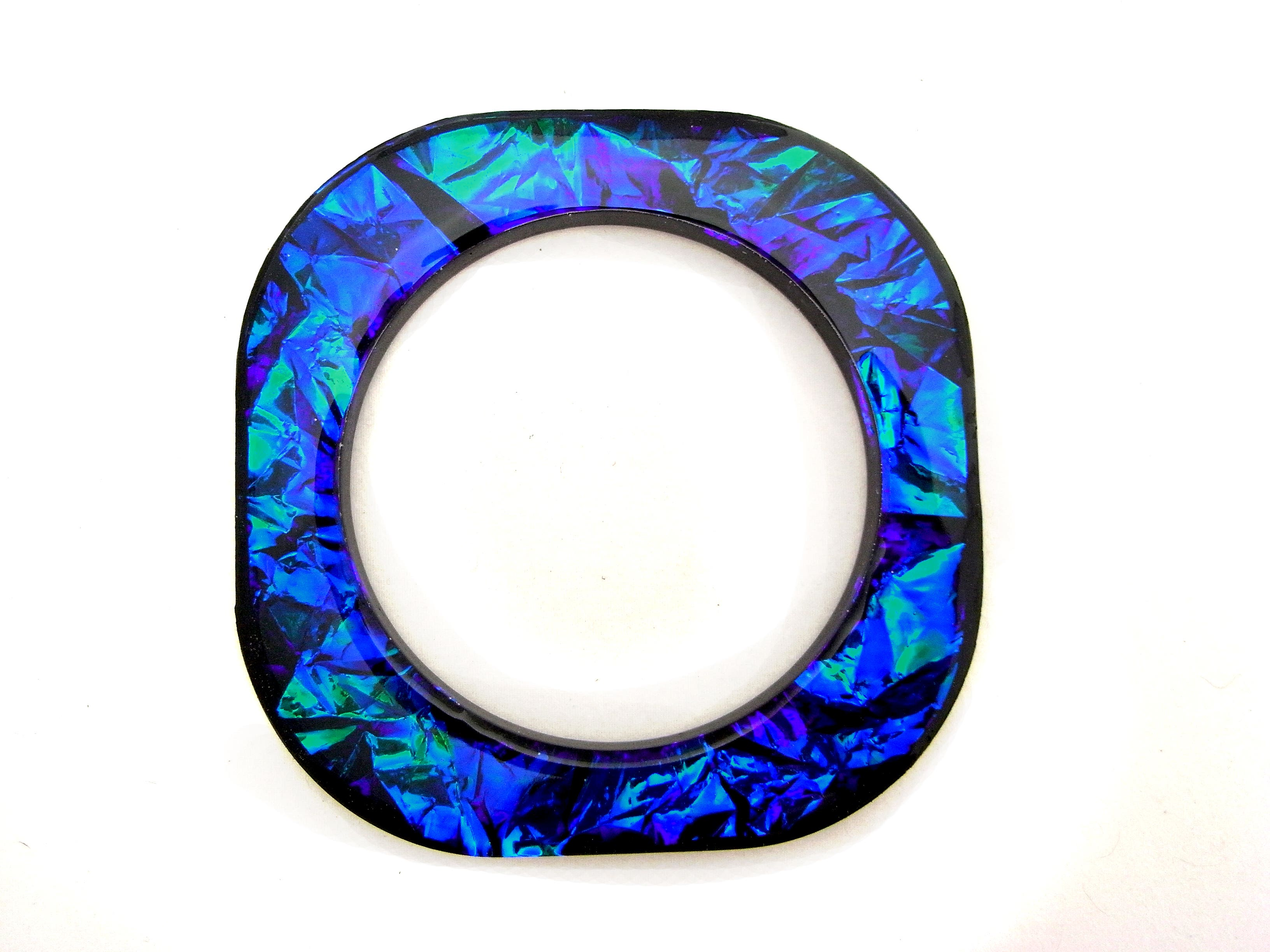Flat square bangle with rounded corners filled with iridescent film in peacock colours.Iridescent