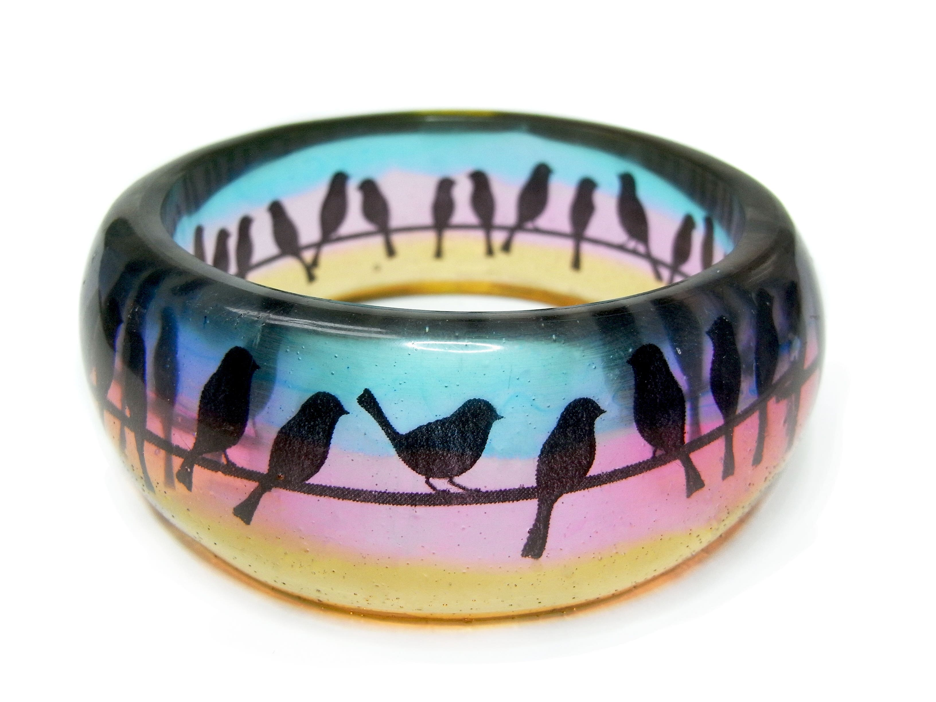 Transparent resin bangle with birds on a wire silhouetted against a gradient background of pink, blue and orange