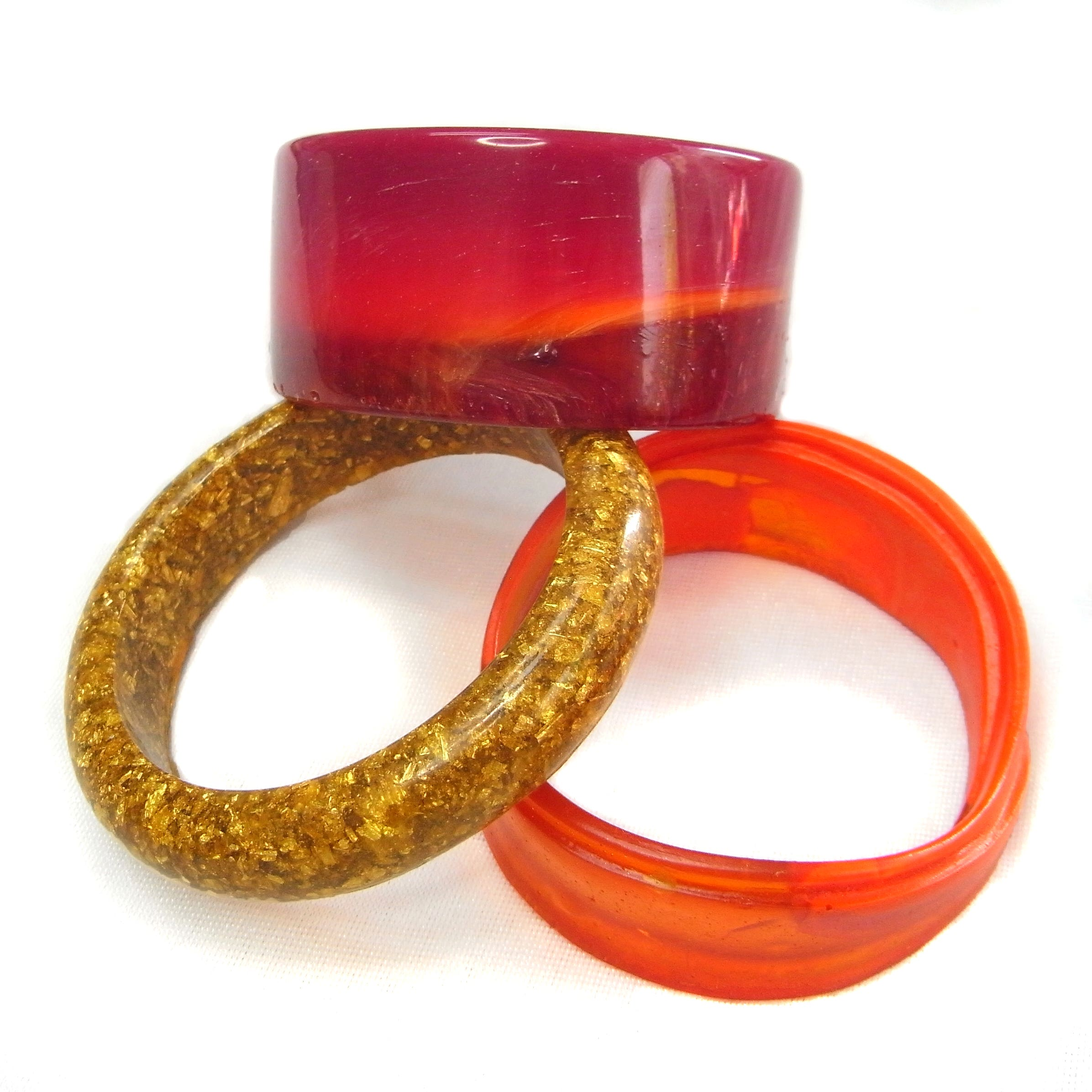 Tri of bangles in shades of burgundy, orange and gold