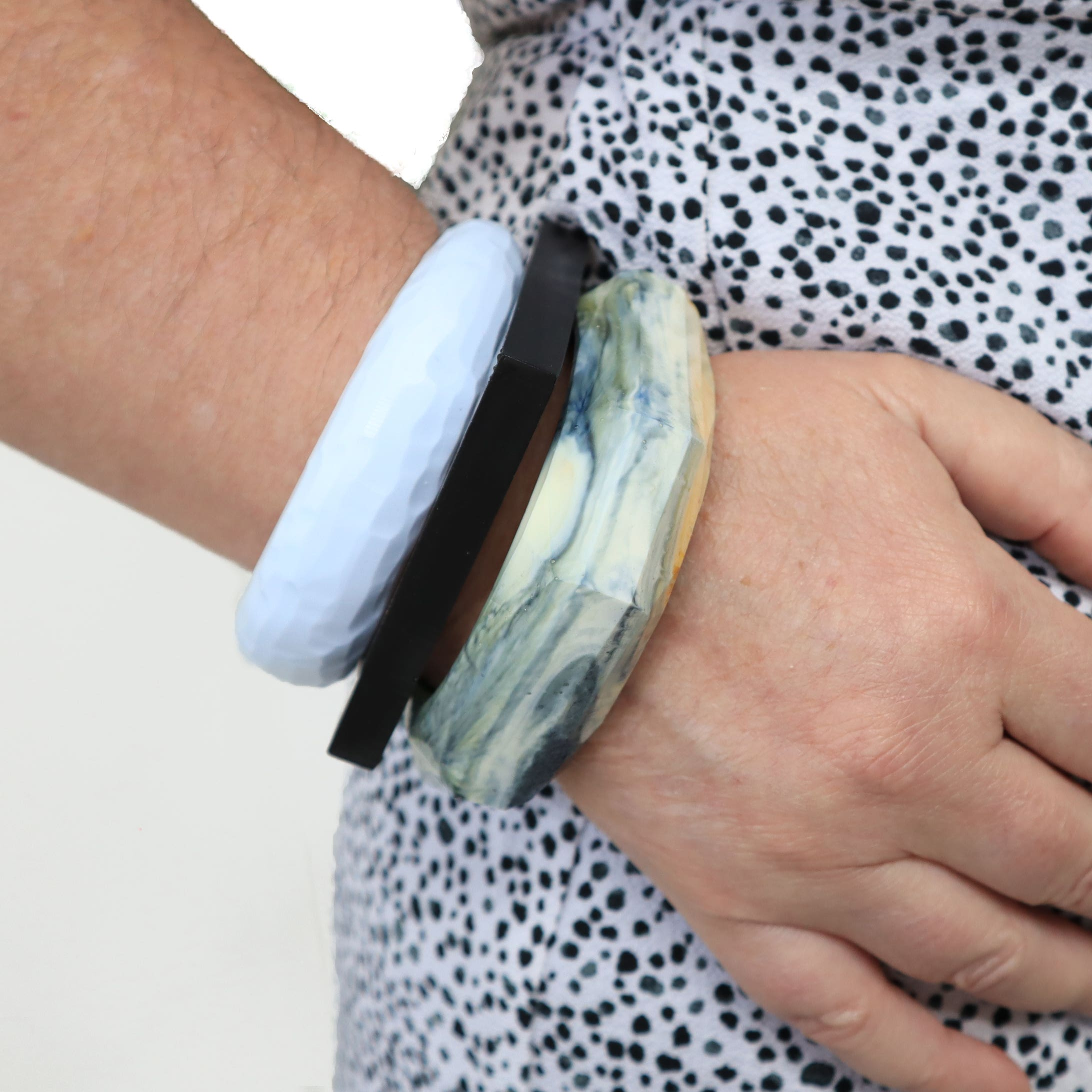 Model wearing stack of bangles in ice blue, black and marbled navy and white
