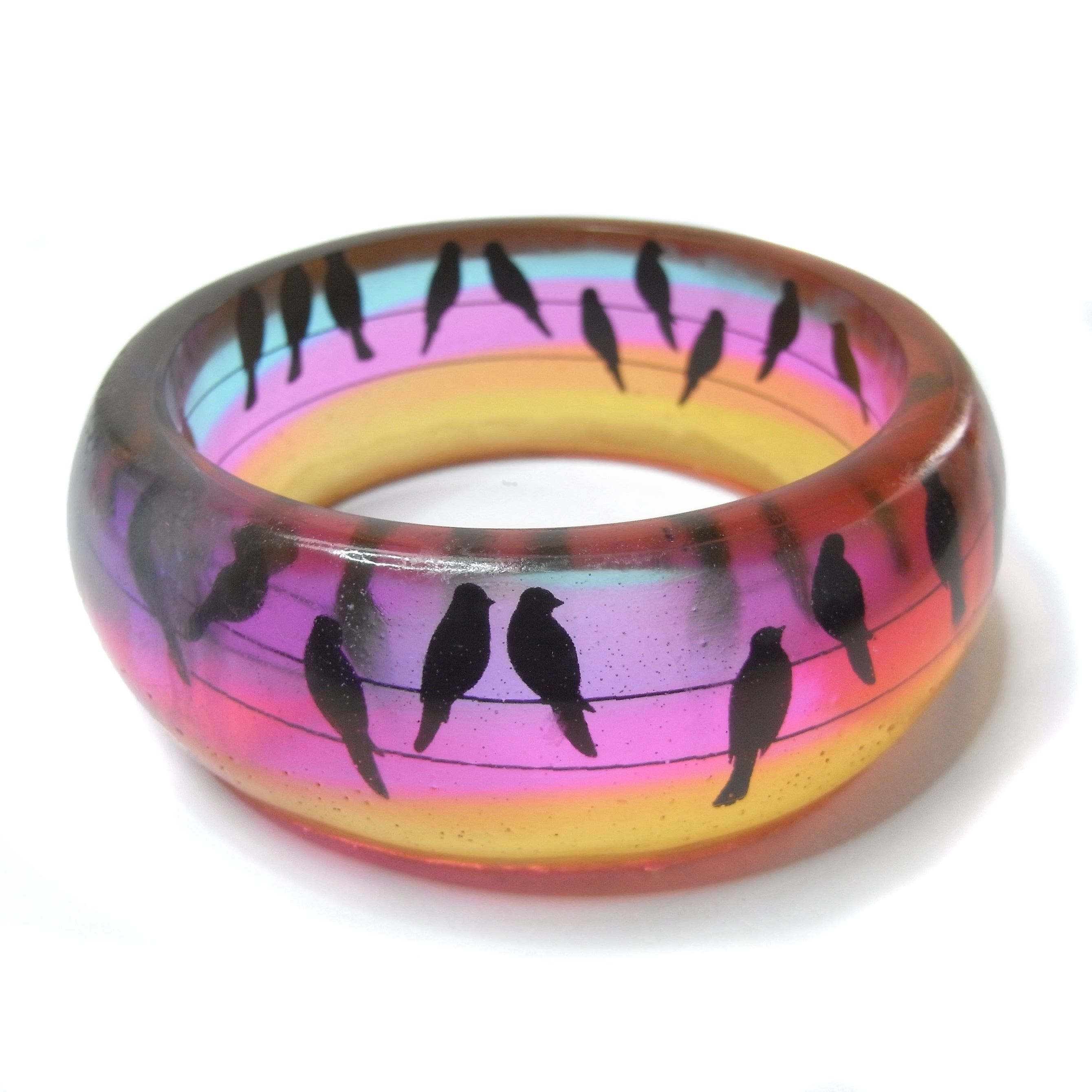 Resin Bangle with silhouette birds on a wire against a sunset sky of orange, pink, purple and blue