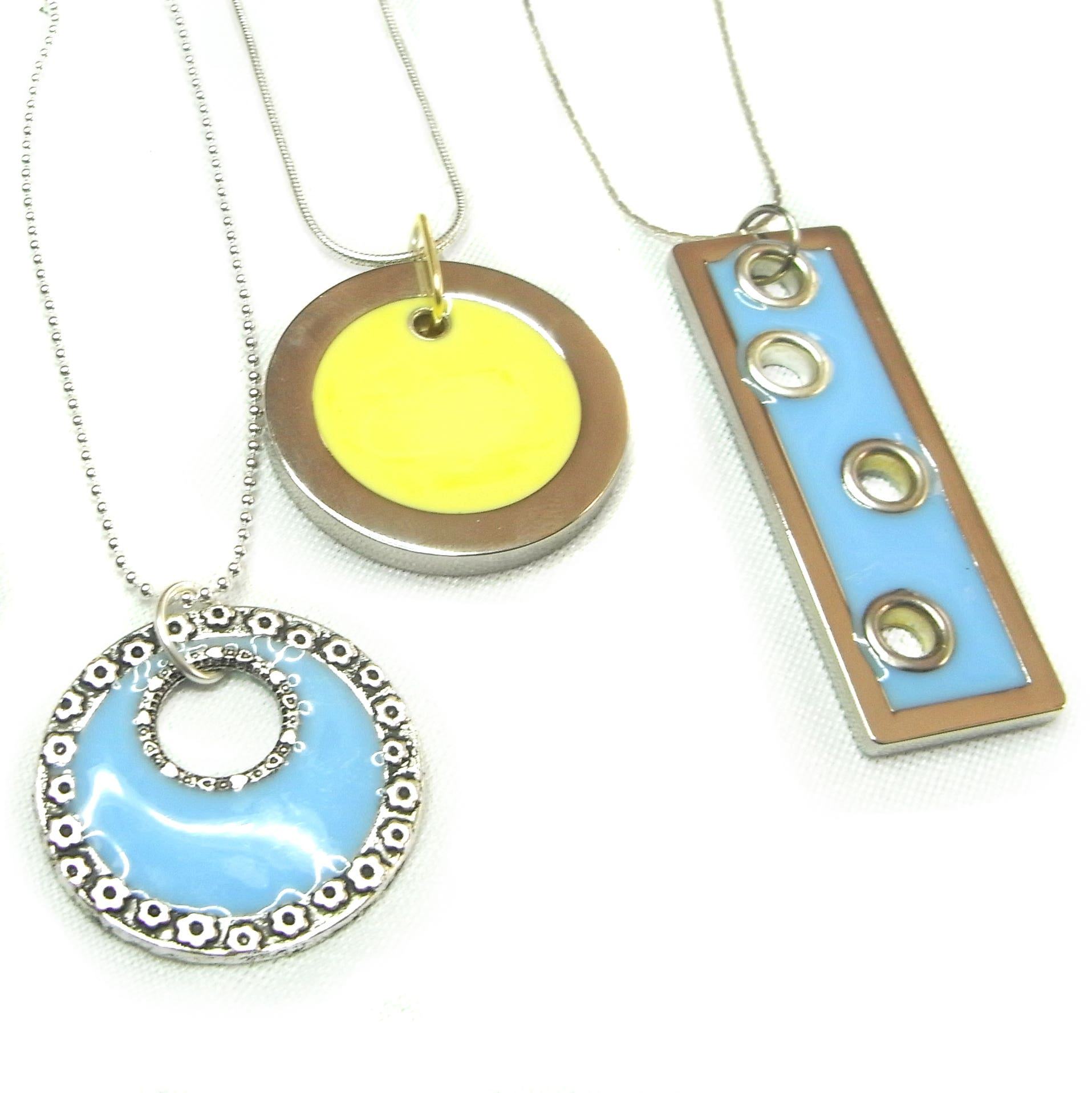 2 circle pendants in pastel yellow and pastel blue and a rectangular blue resin pendant inset with grommets