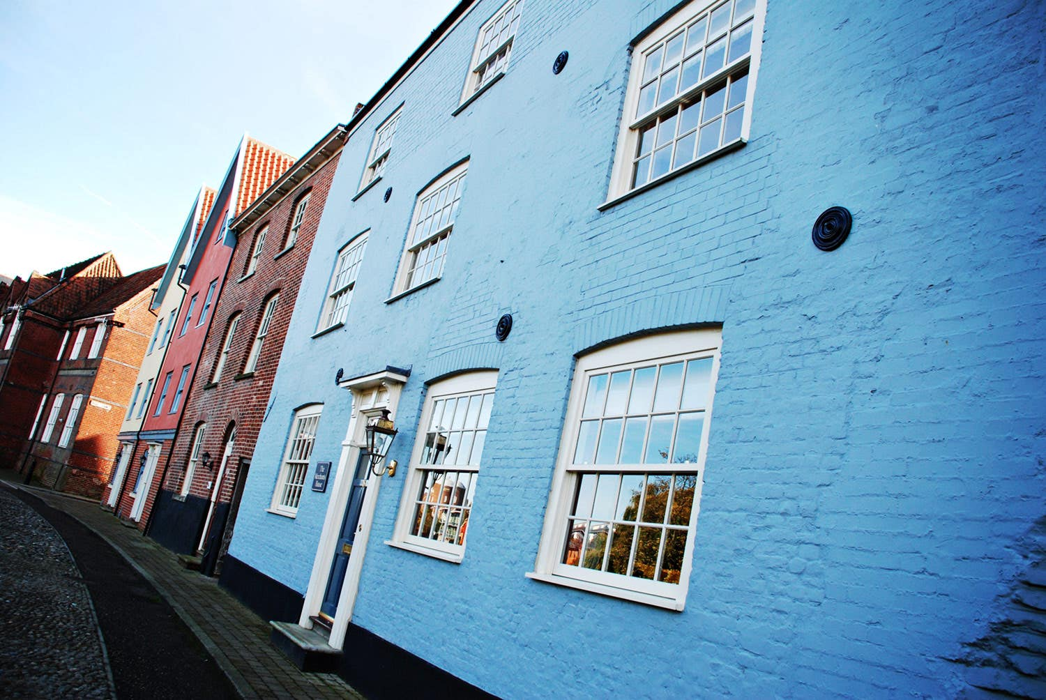 A row of colourful buildings photographed at a tilt from the side