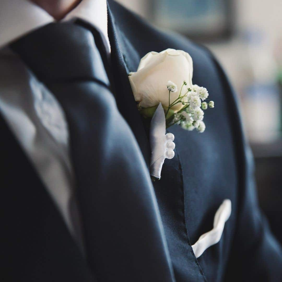 Groom in navy suit with rose button hole and tie