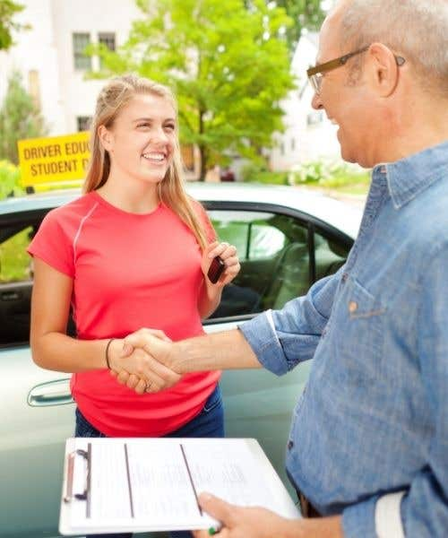 teen driver shaking hands with examiner