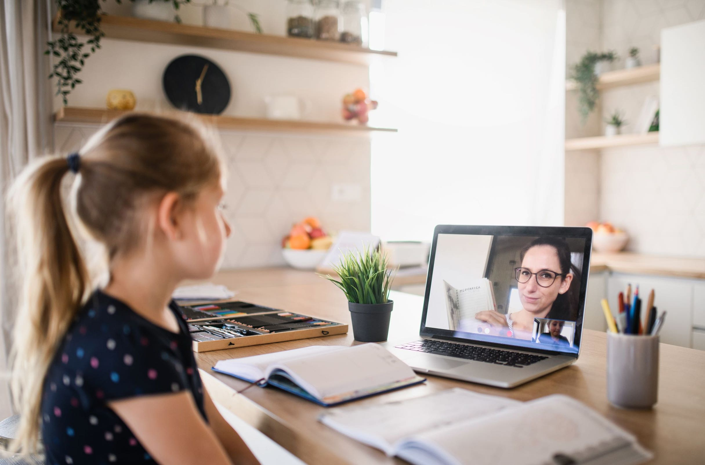 Girl remote learning watching teacher on screen