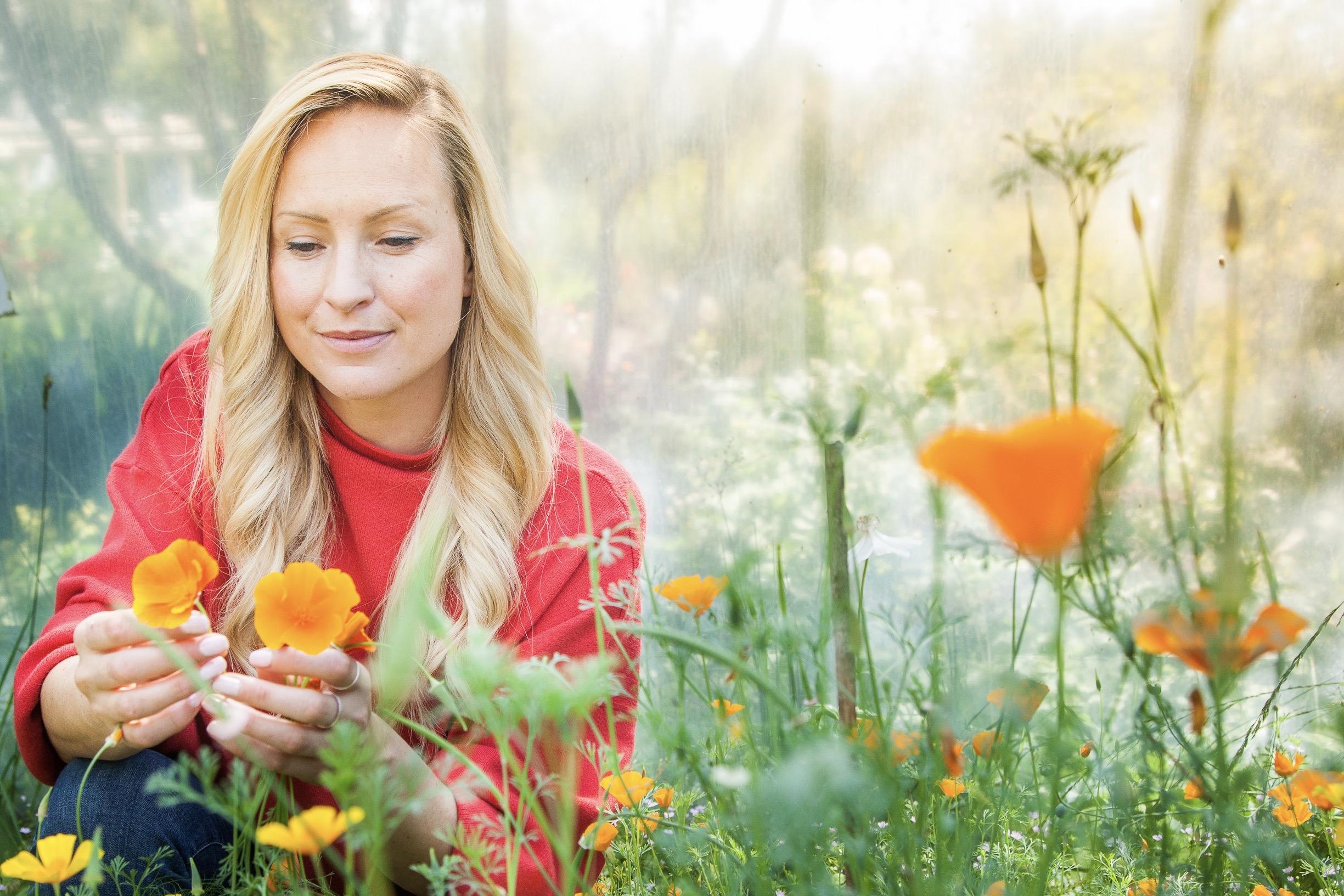 garden designer Leonie Cornelius in a poytunnell pocking some Californian poppies