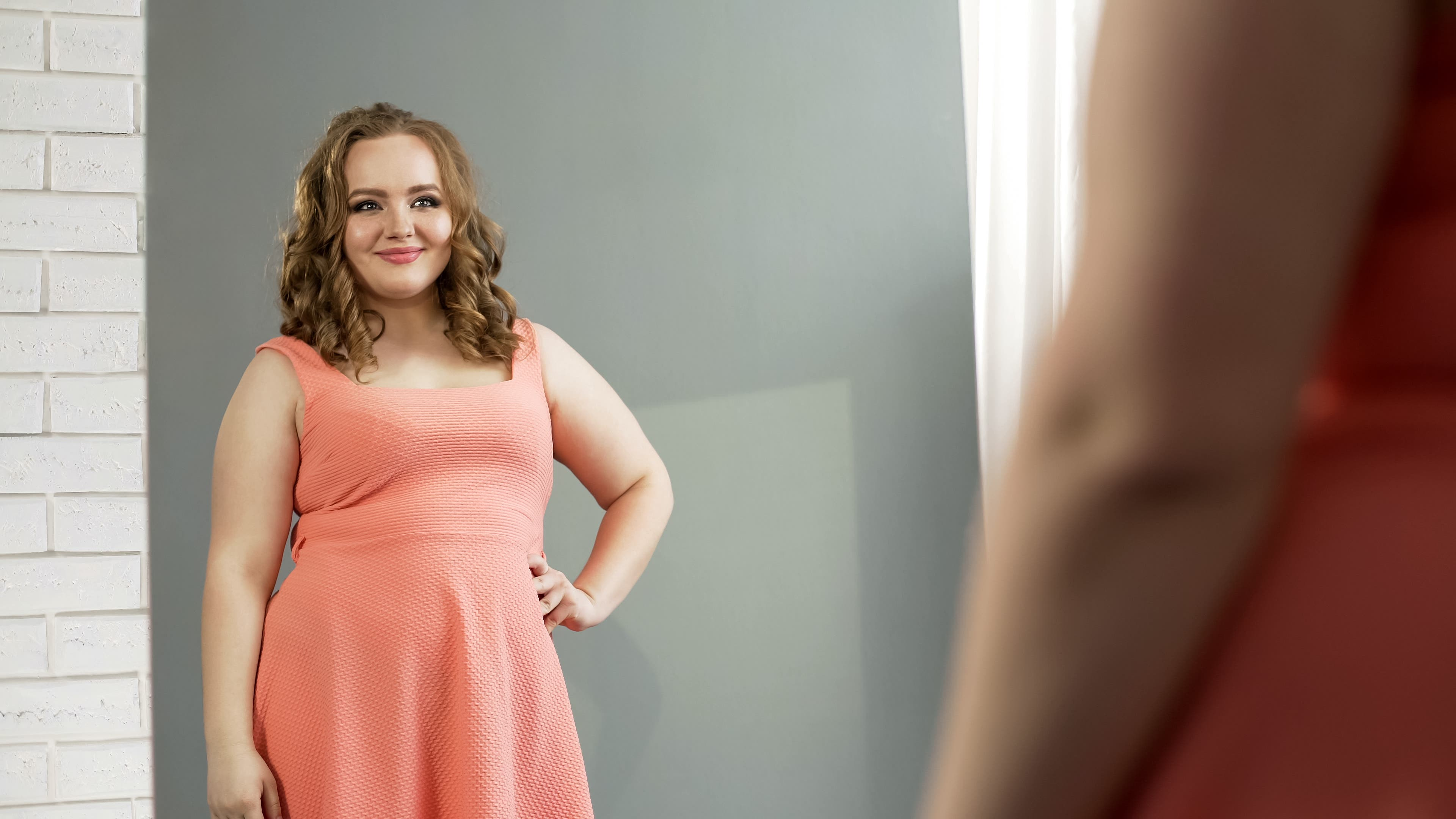 Confident woman looking in the mirror. Lost weight, feels confident, and loves herself.