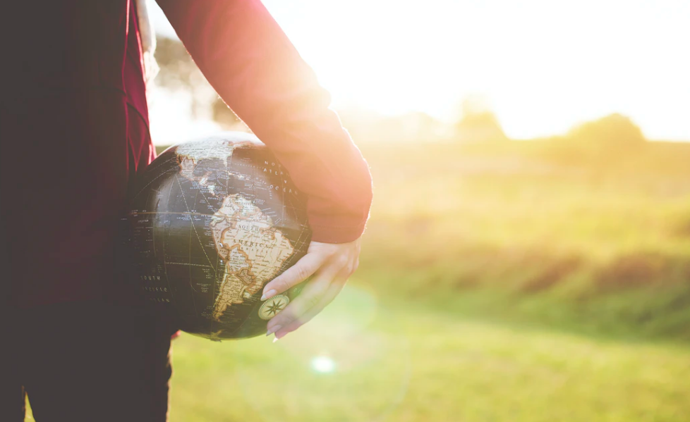 person holding a globe of the Earth
