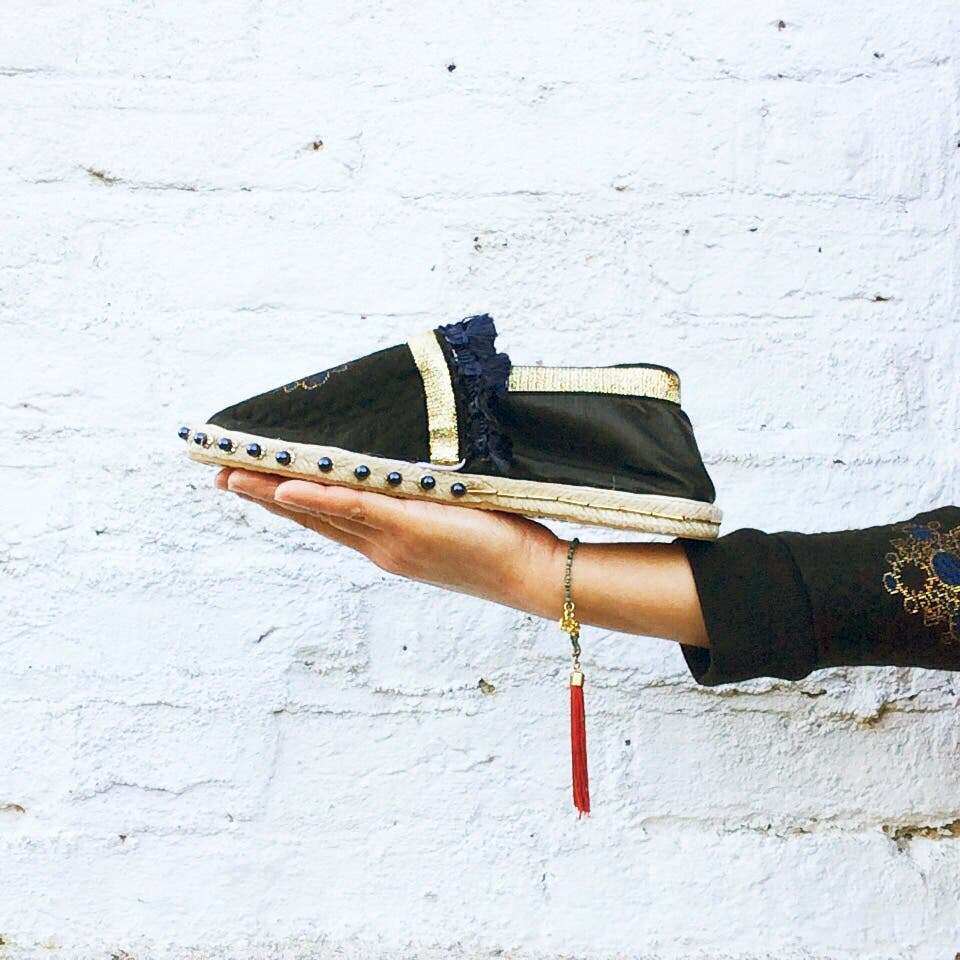 Cropped photo of outstretched arm holding a handmade shoe against a white brick wall