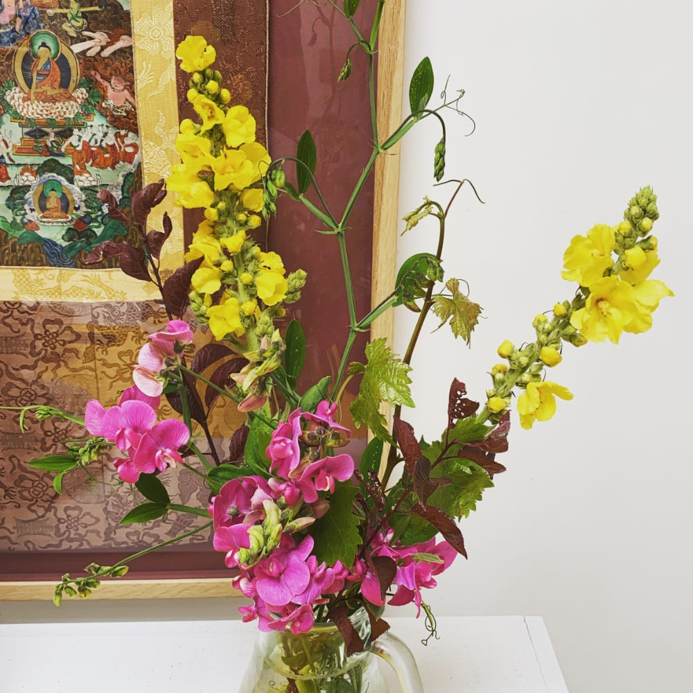 pink sweet peas and yellow mullein on the shrine in front of corner of buddhist hanging