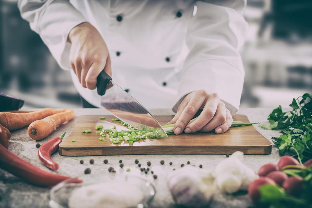 chef cortando hortalizas con un cuchillo