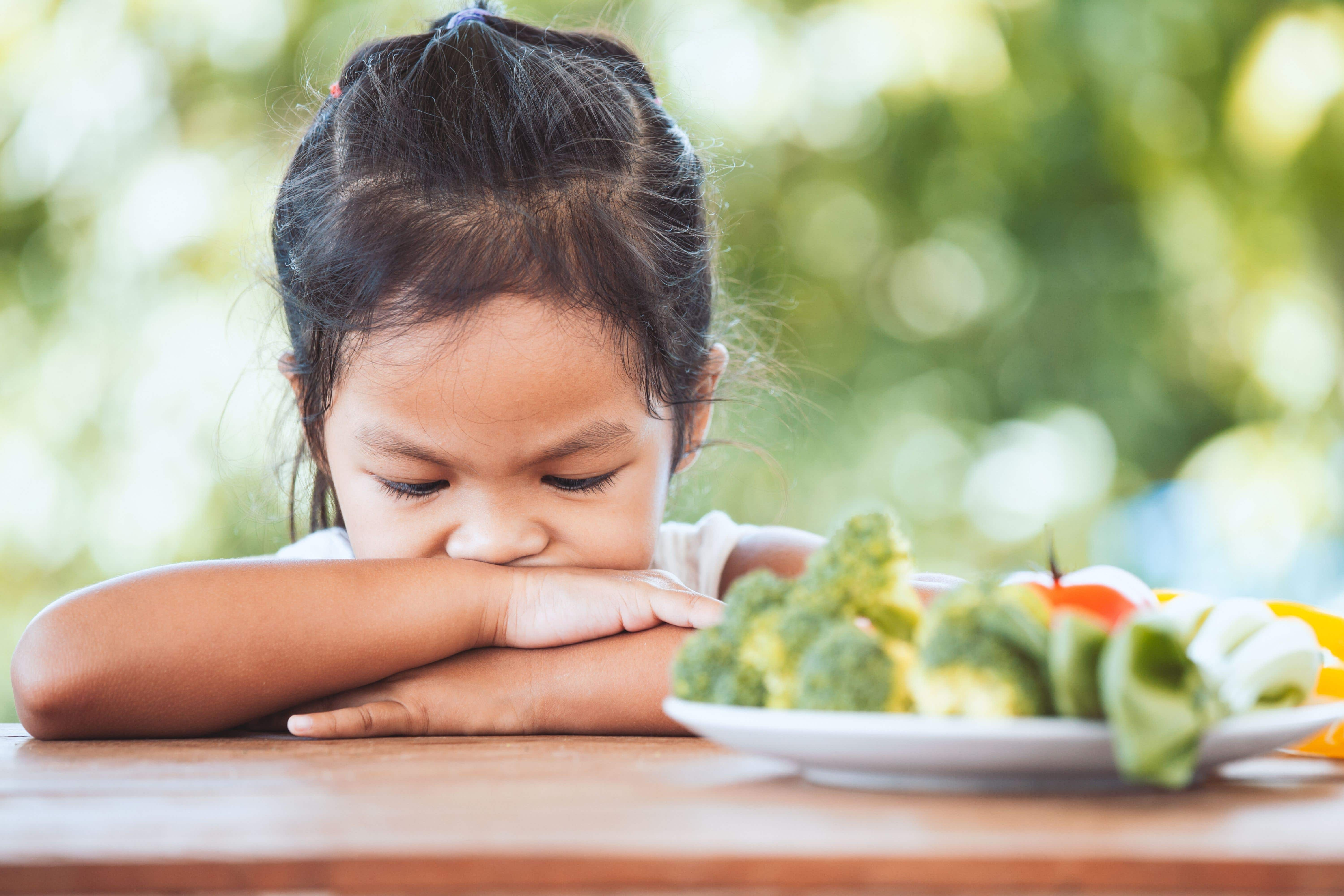 Child pushing away a plate of vegetables