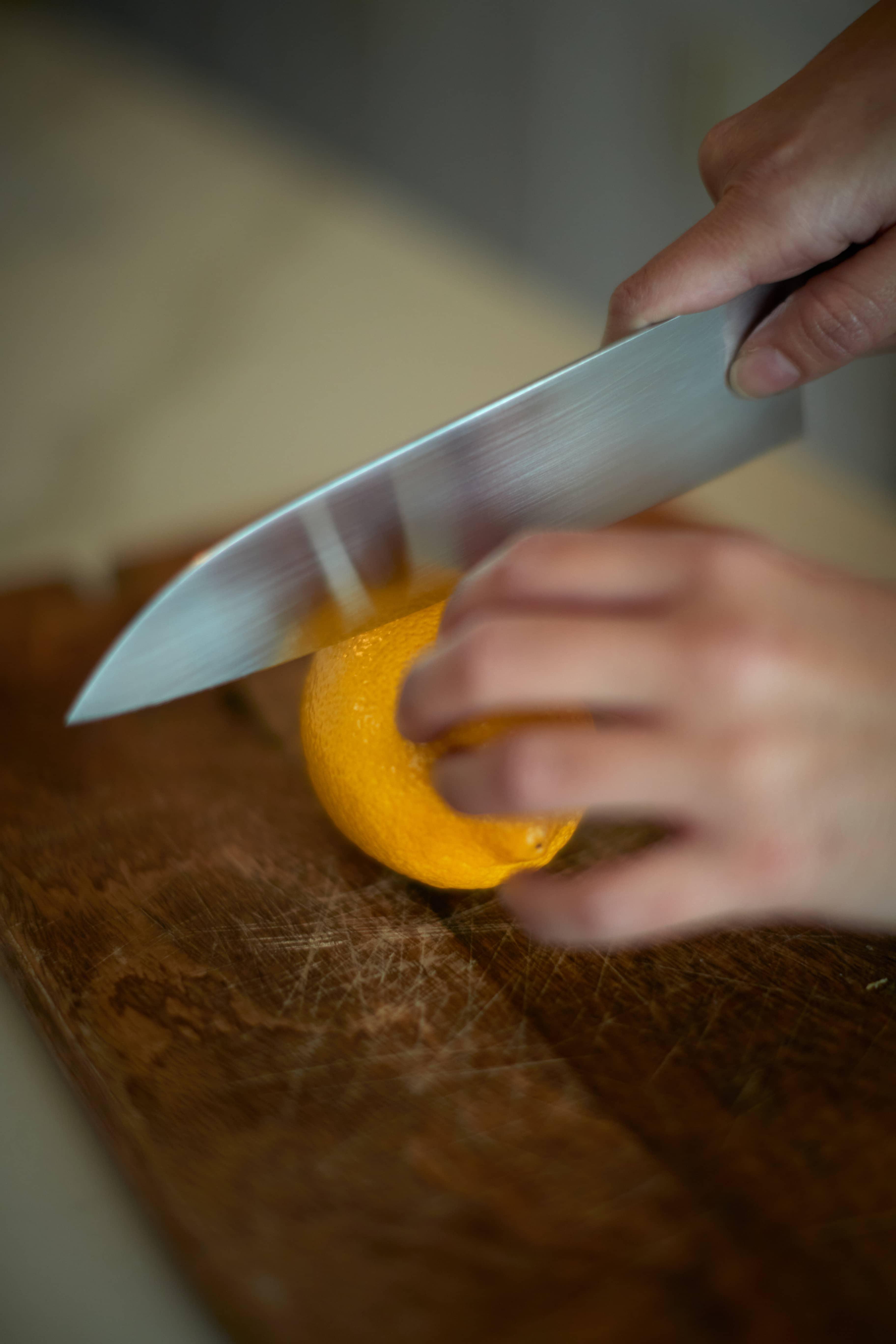 Knife slicing through an orange
