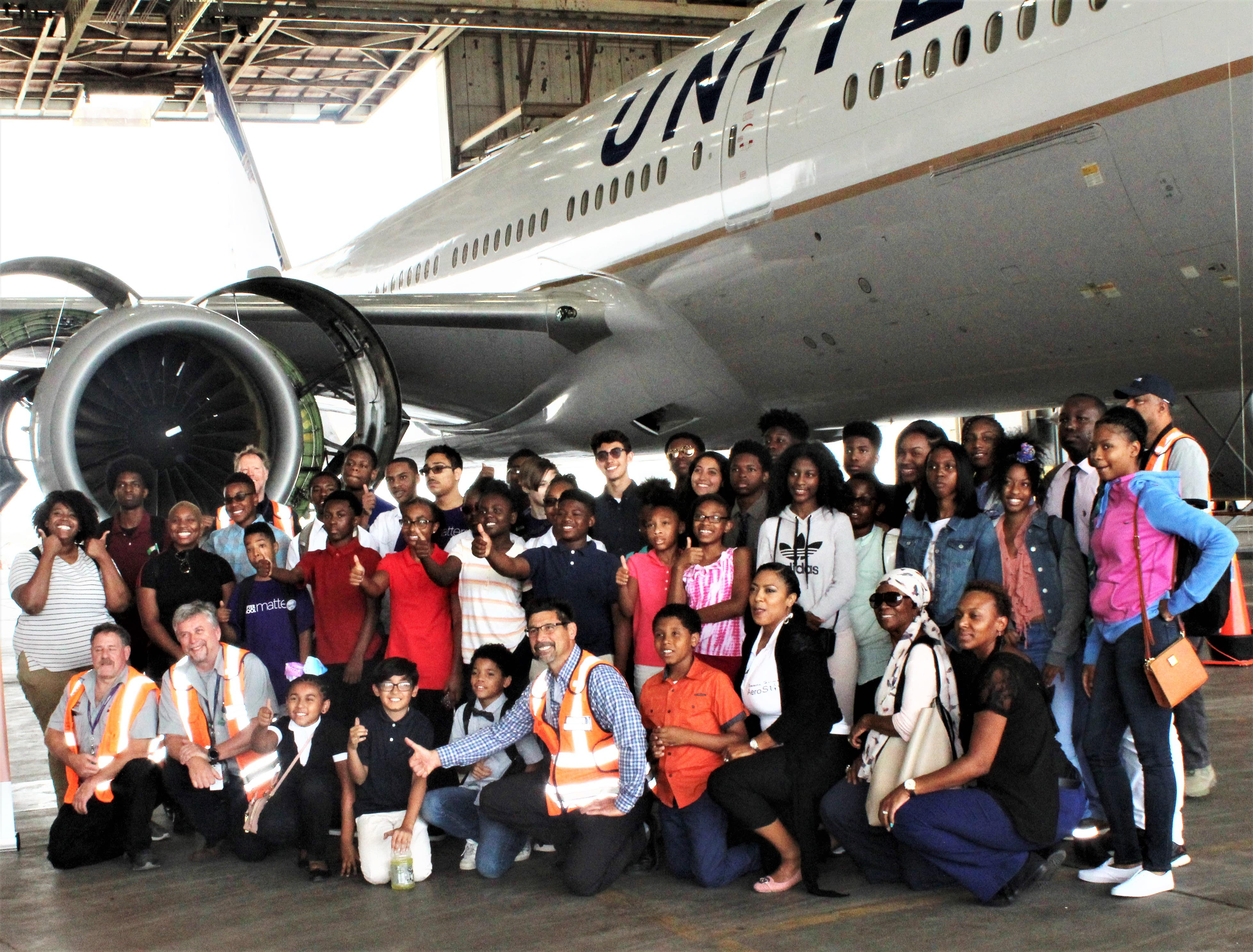 A class of students and teachers smiling in front of a plane