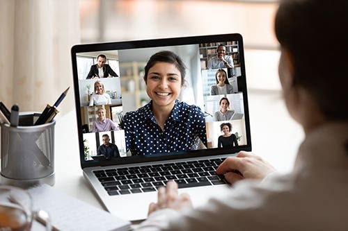 Woman at Desk with Laptop Showing Video Conference