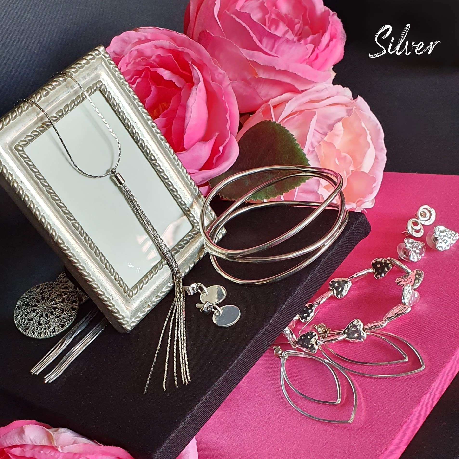 Group of of silver jewellery and gifting on a pink and black background