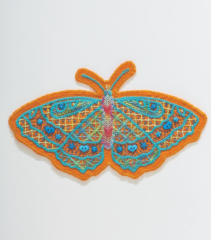 Embroidered butterfly in mainly light blue thread on orange wool felt