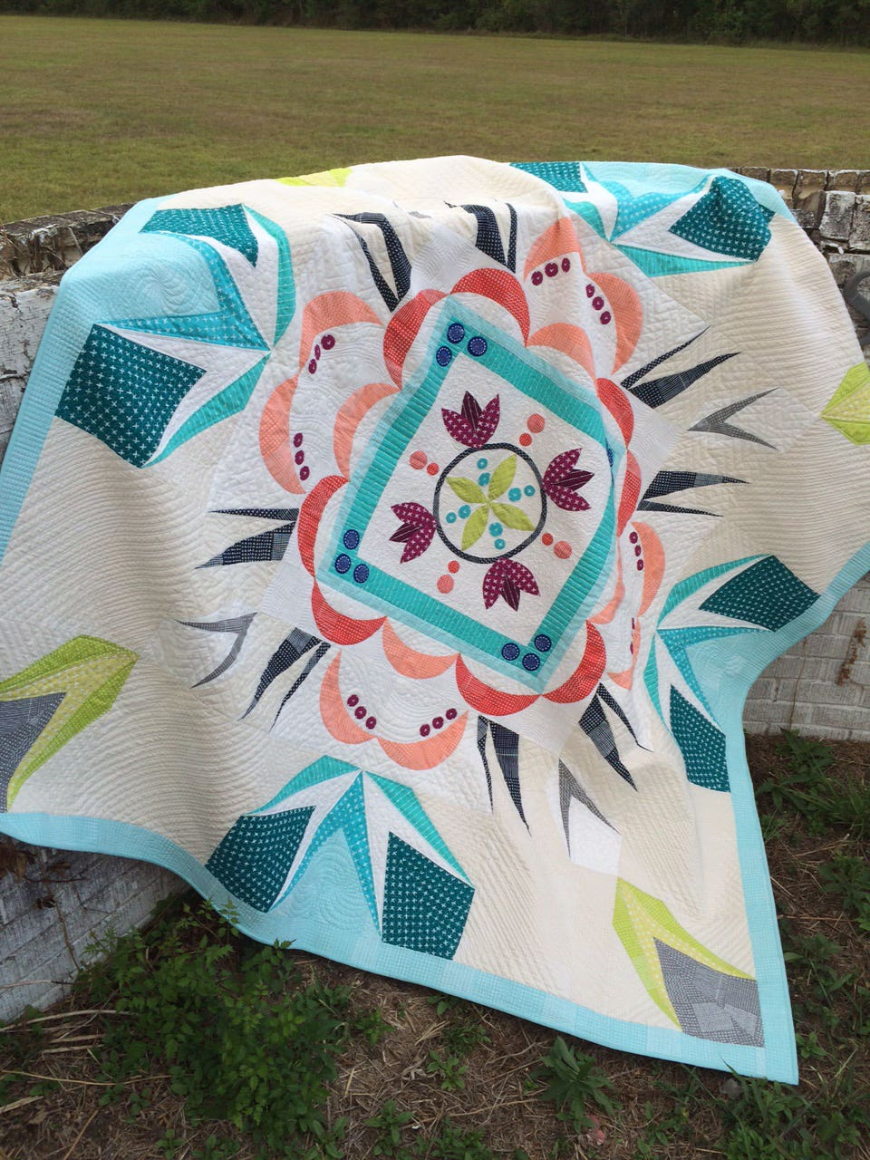 Quilt draped over a stone wall outdoors.