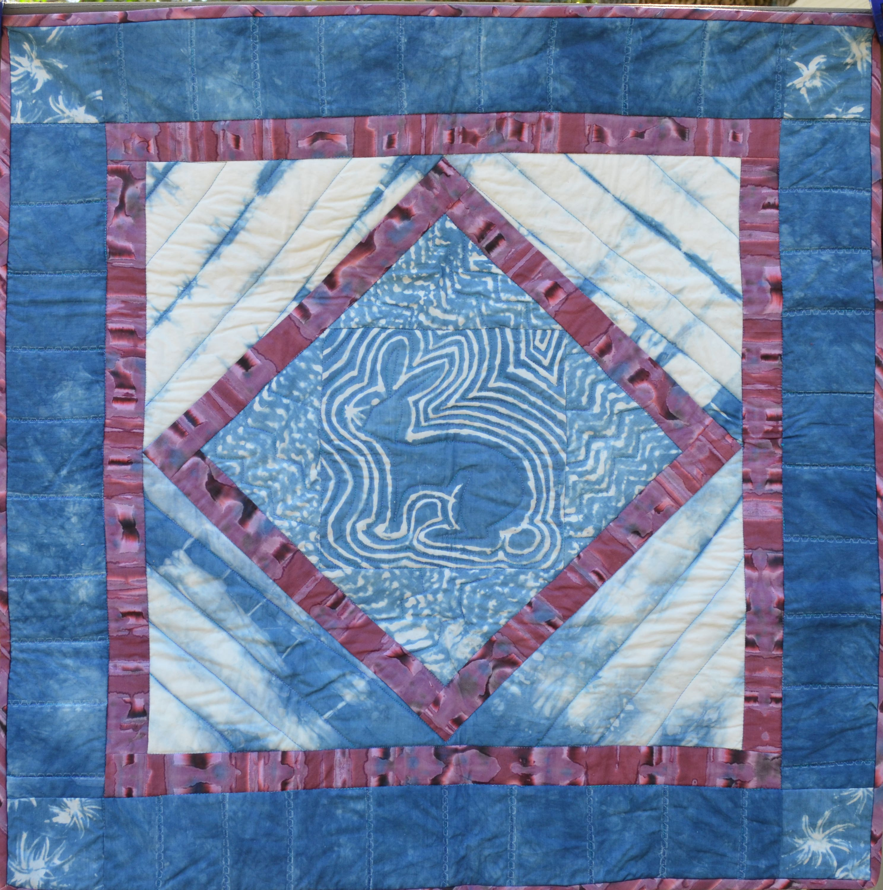 Small quilt with several indigo dyed fabrics. The central fabric depicts an outline of a rabbit dyed in the fabric using the resist technique.