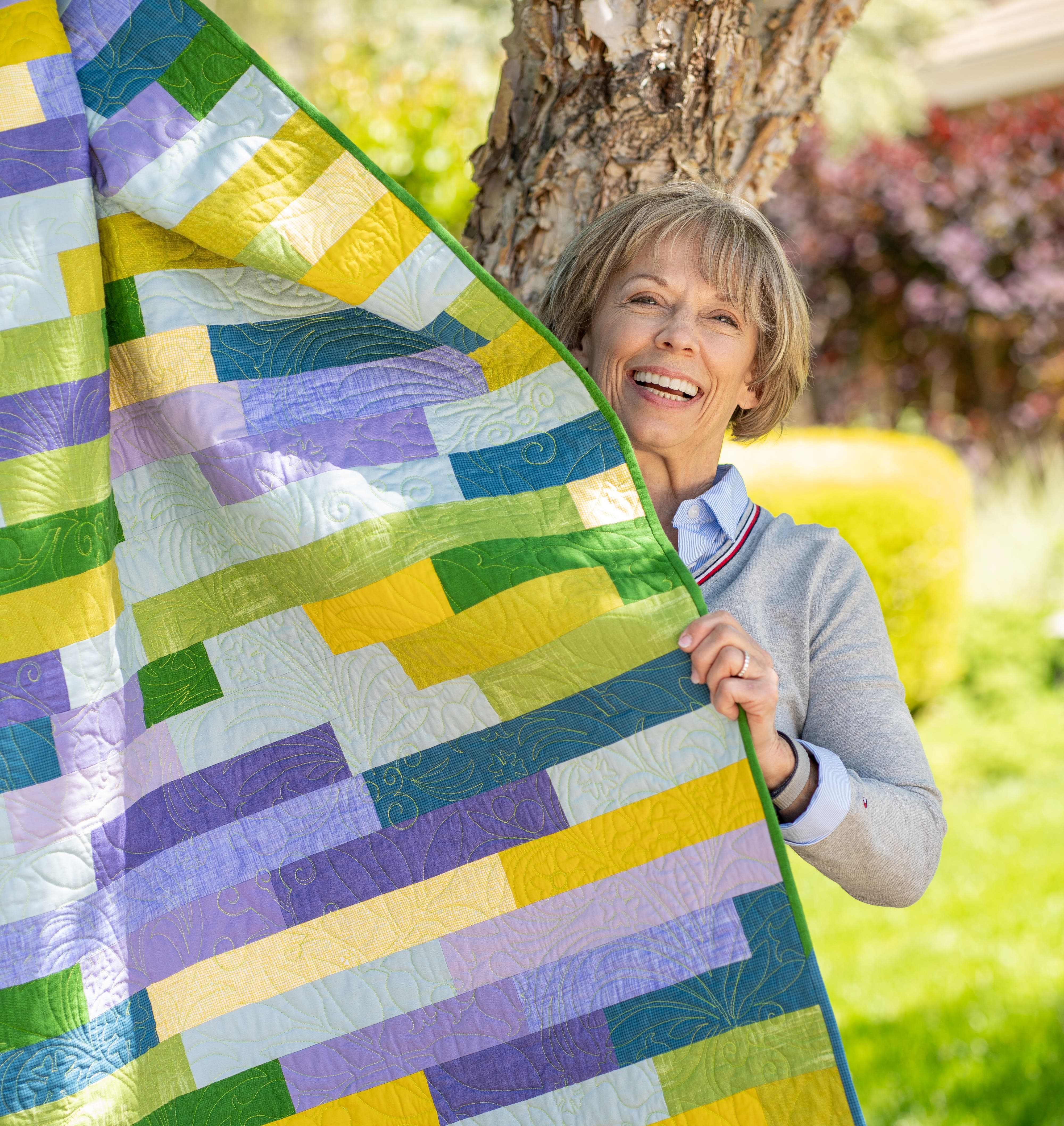 Jenny Lyon smiling and holding a free motion quilted quilt in green, blue, purple and yellow