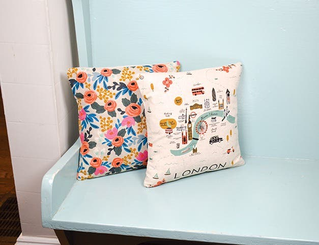 Two pillows on a light blue bench