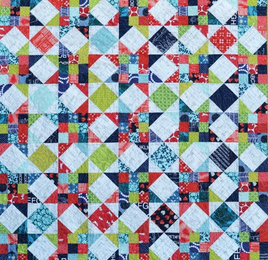 Scrappy star quilt in reds, greens, dark and light blues.