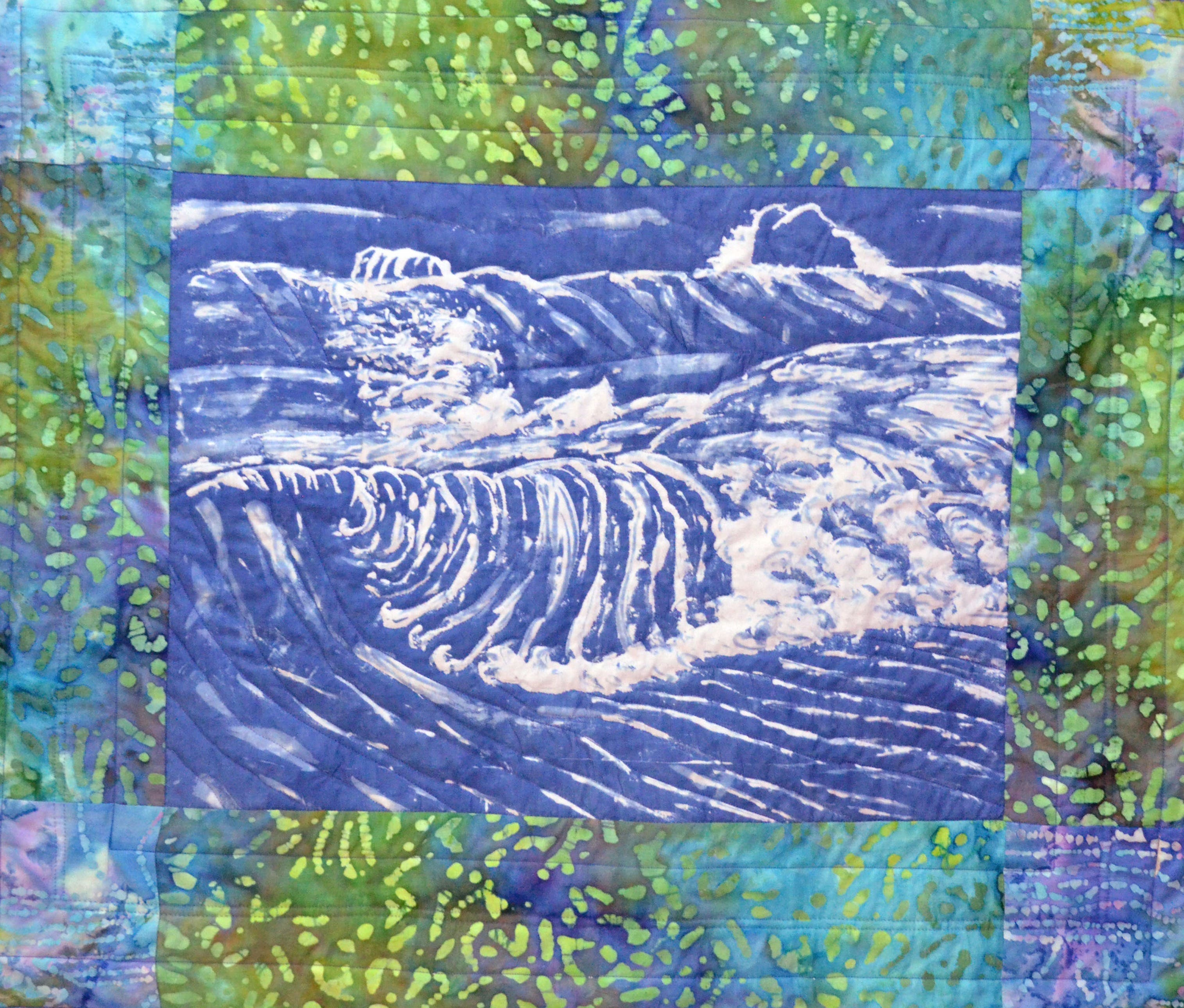 Small quilt of an indigo dyed fabric with a scene of an ocean wave bordered in batik fabric.