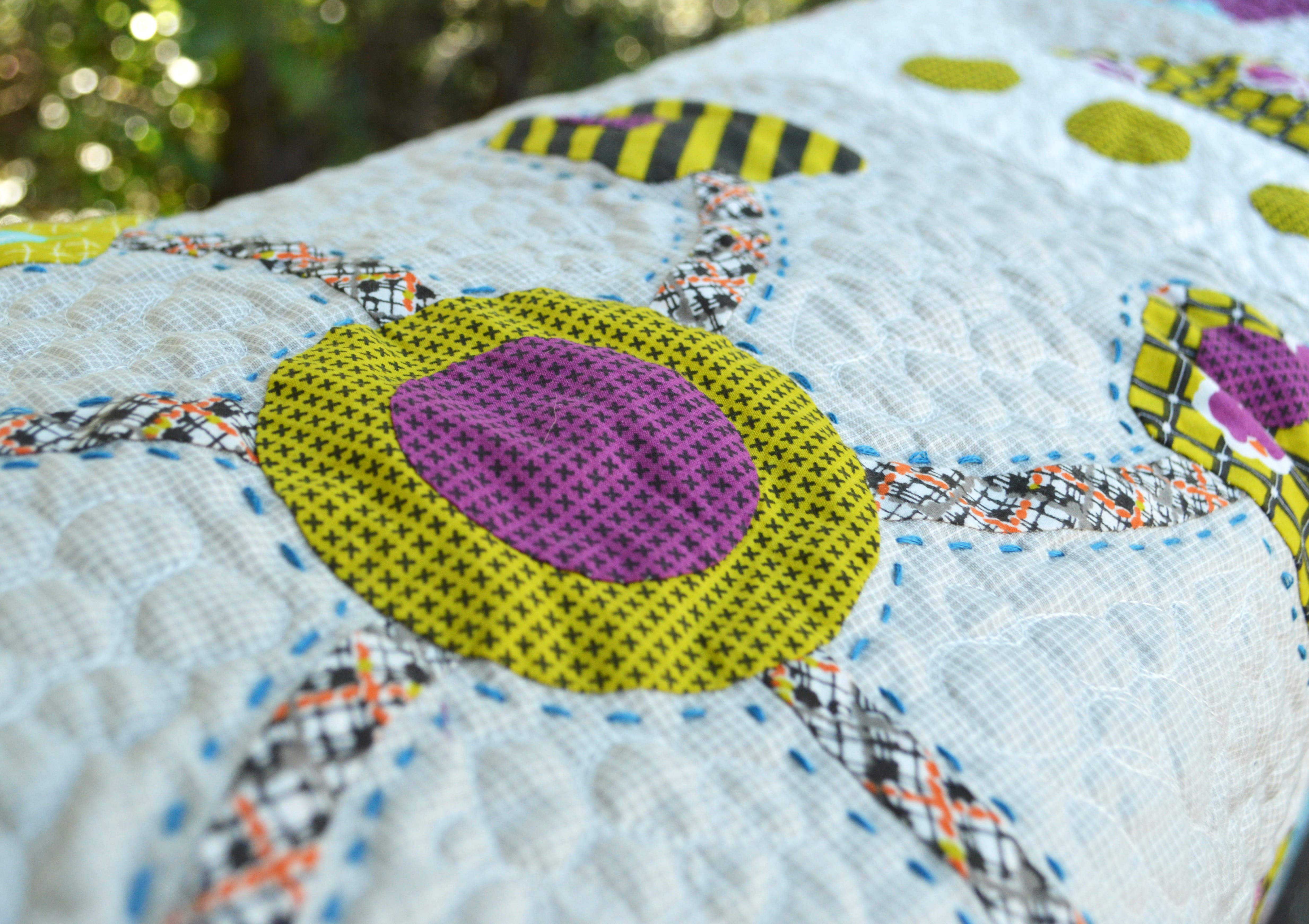 Close up on applique on a quilt with hand and machine quilting