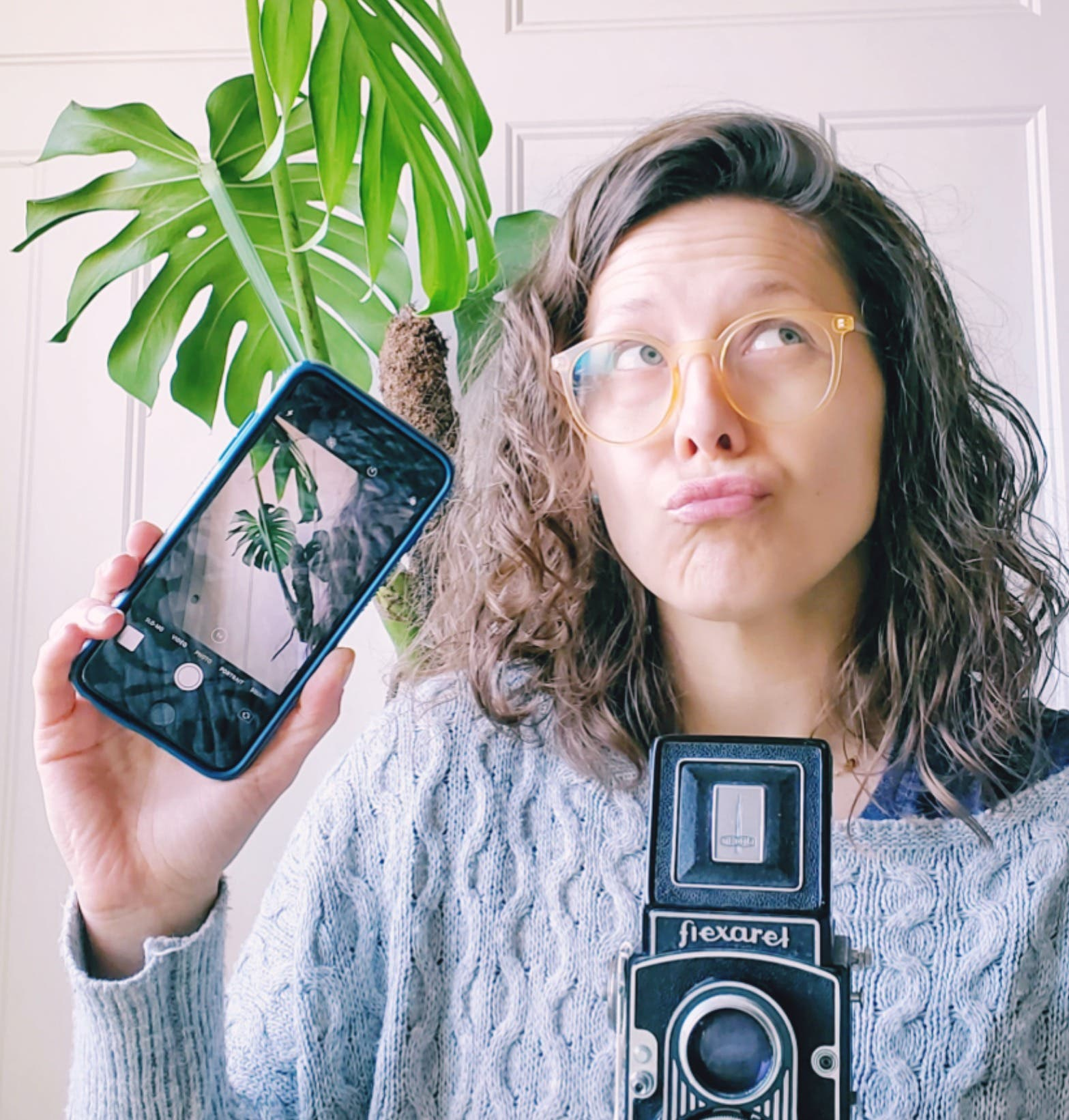 Andie Solar holding a cell phone camera in one hand and a Twin Lens Reflex film camera in the other hand.