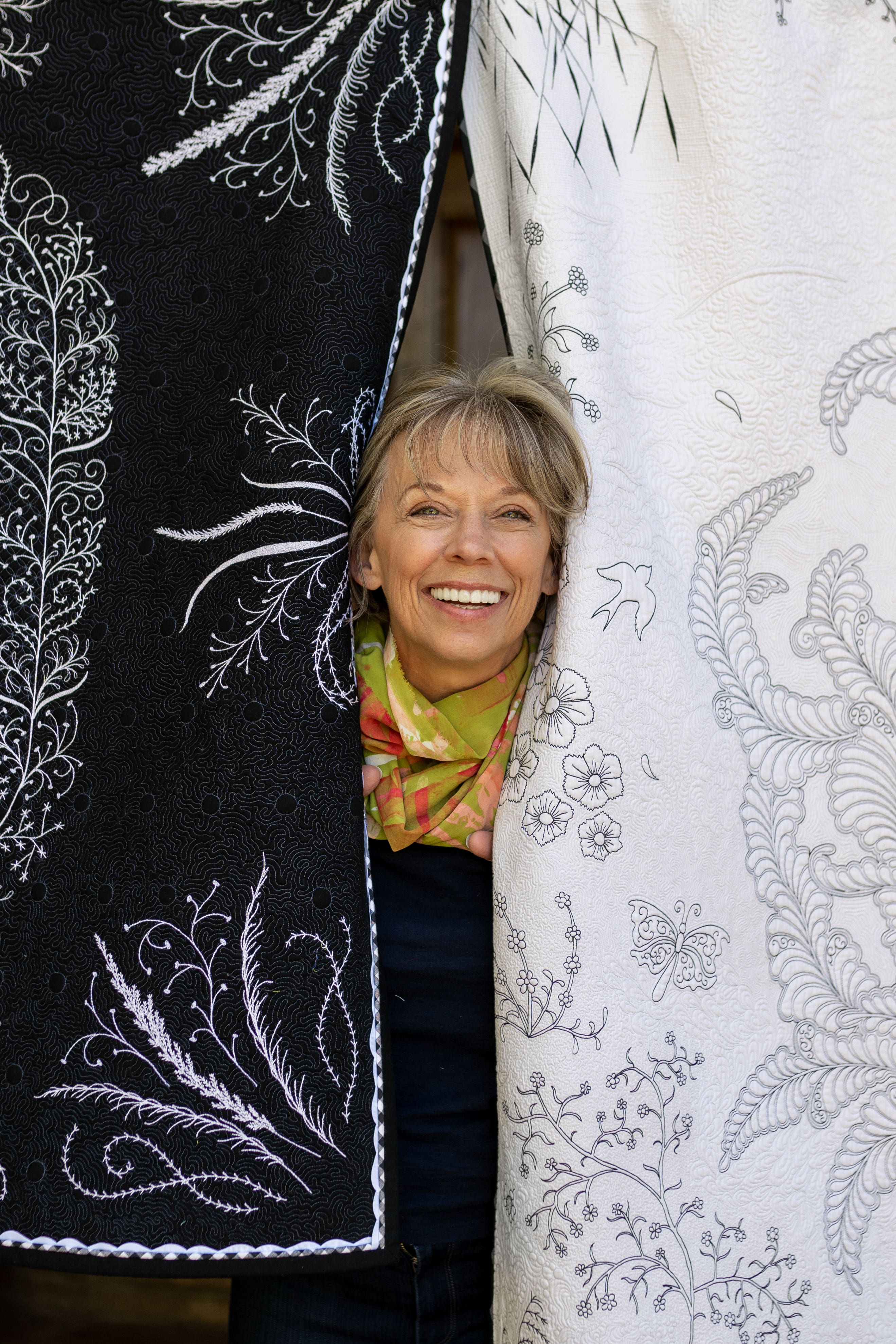 Jenny Lyon peeking out from between two very ornately quilted, hanging quilts.