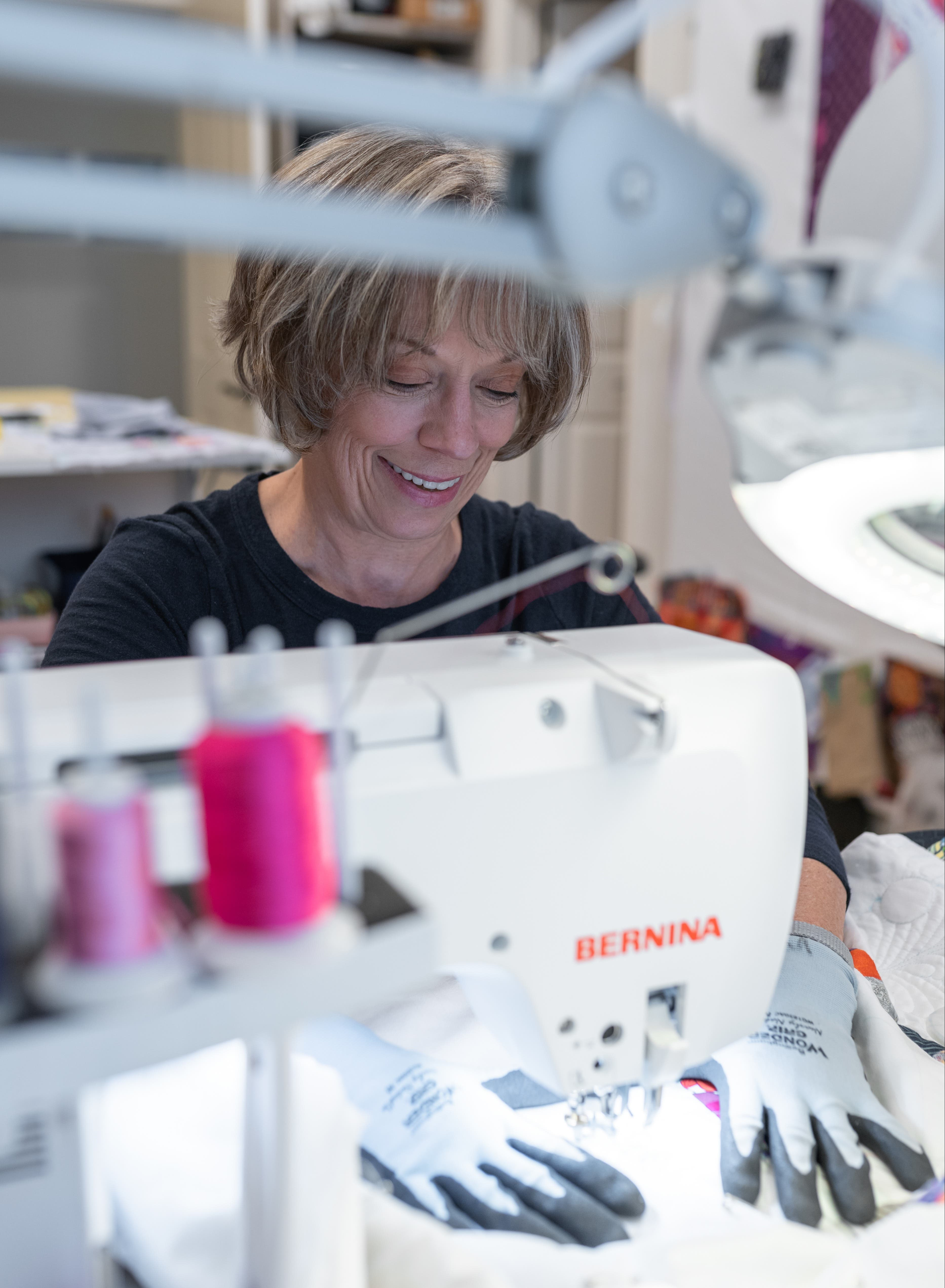 Jenny Lyon free motion quilting at the sewing machine and smiling.