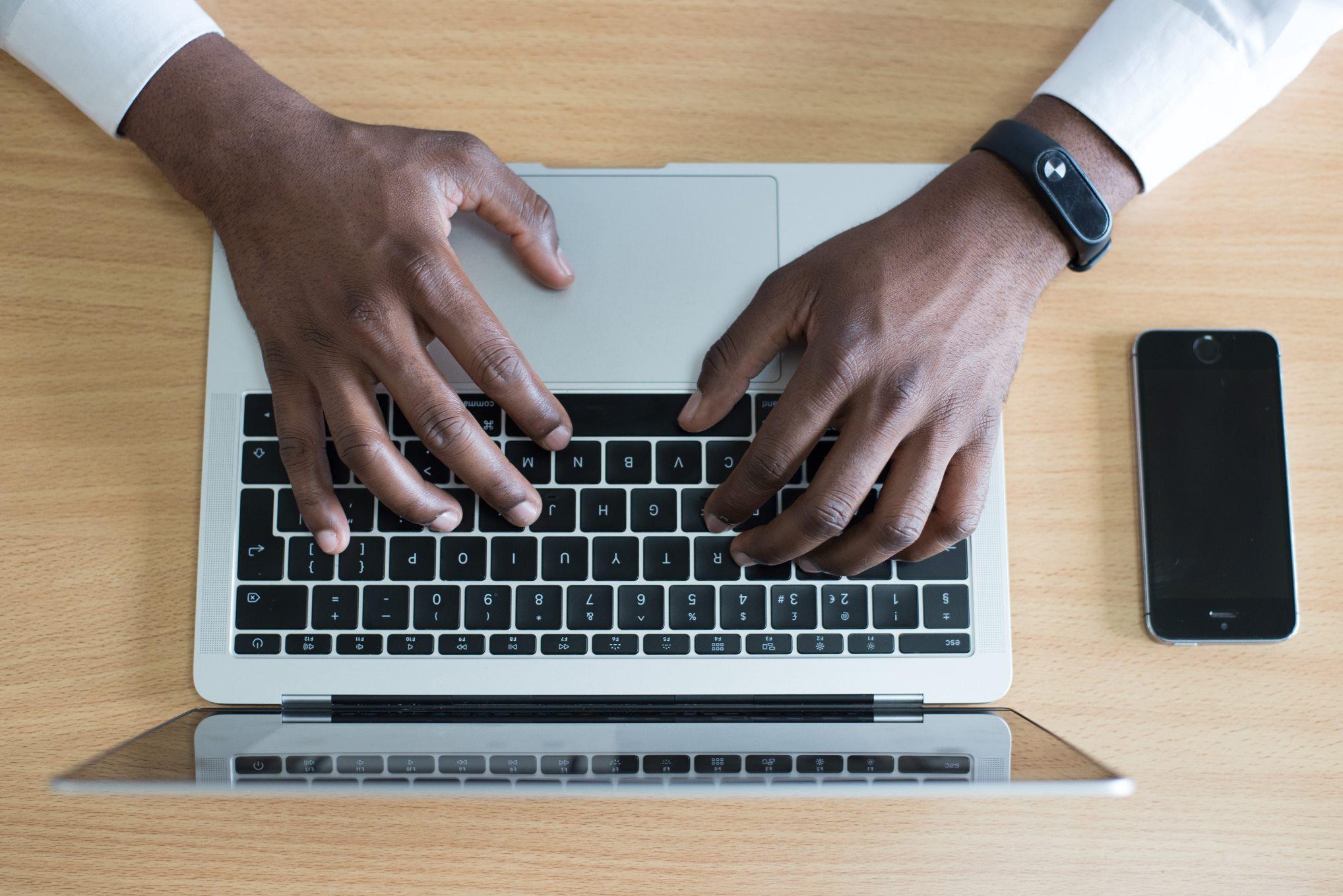 Black Kenyan man typing MacBook smart watch phone