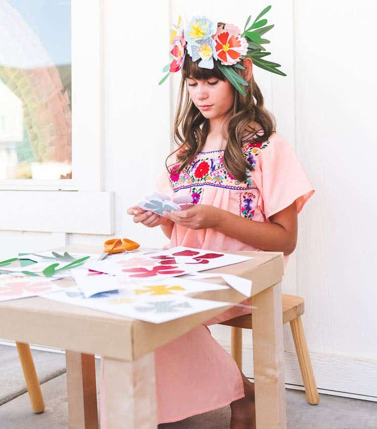 Little girl in pink dress crafting and making a paper crown