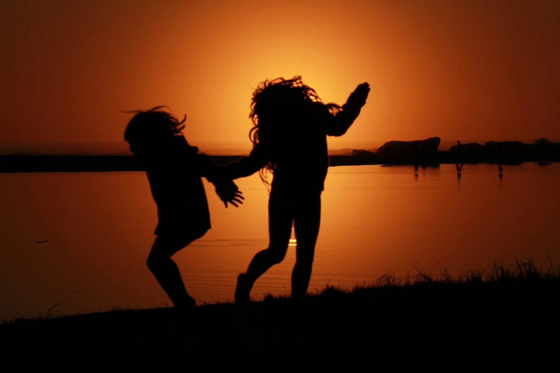sisters jumping silhouette sunset